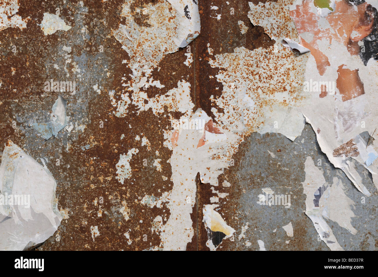 Corroded metal surface with remains of posters Stock Photo