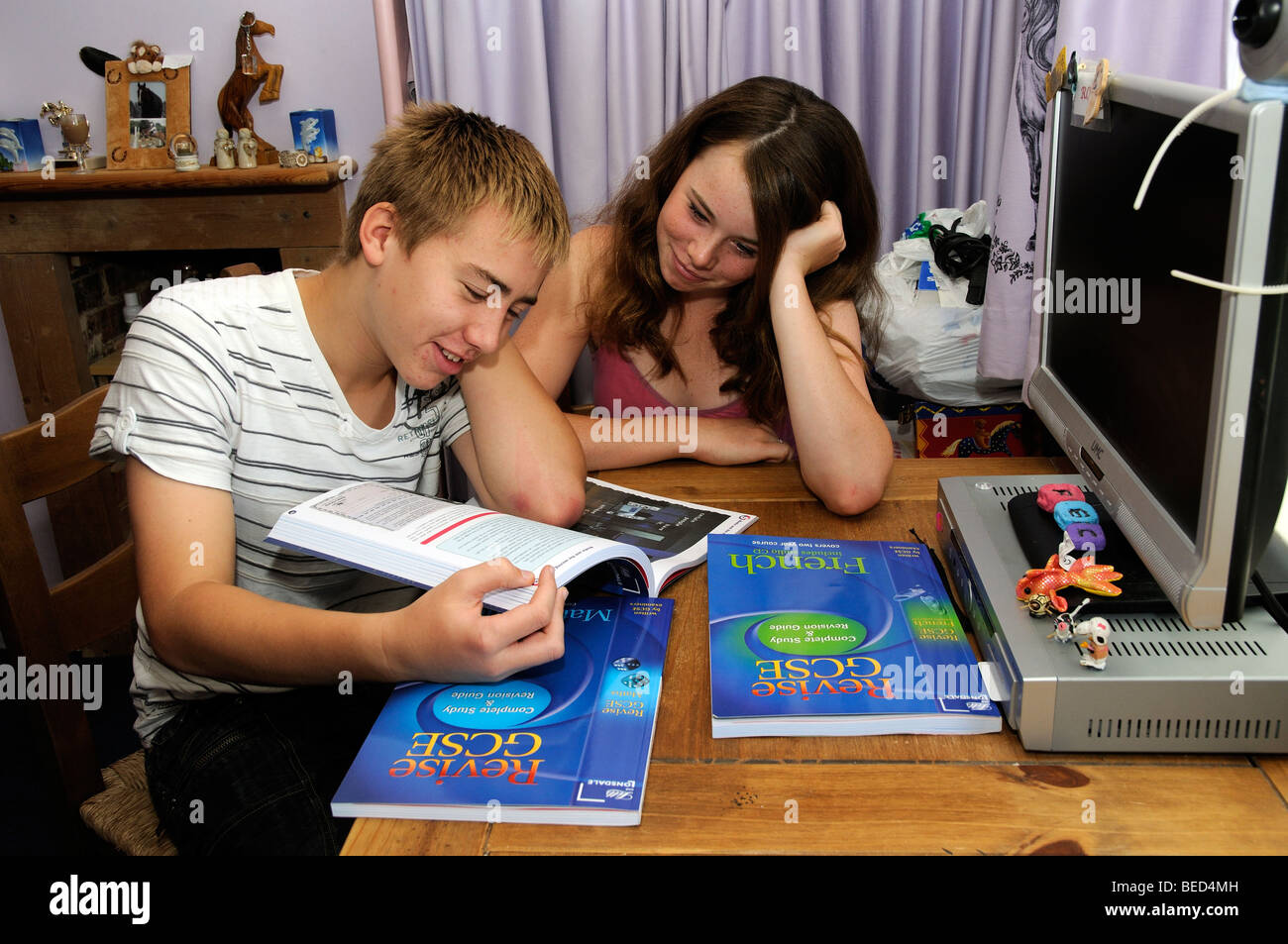 Teenagers revise for GCSE exams Boy and girl students studying at home - Stock Image