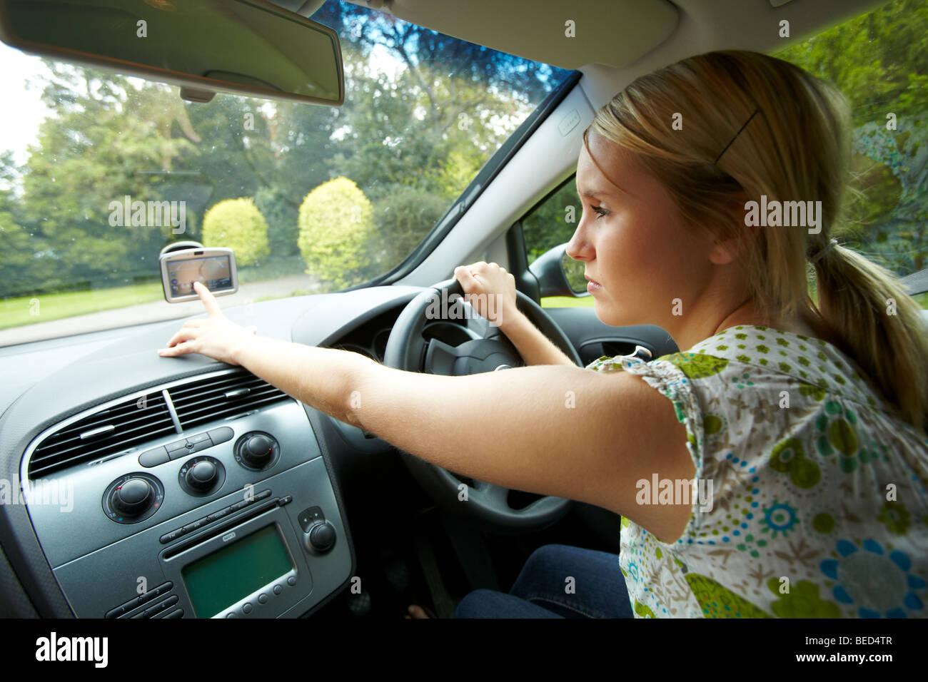 Girl driving car using phone - Stock Image
