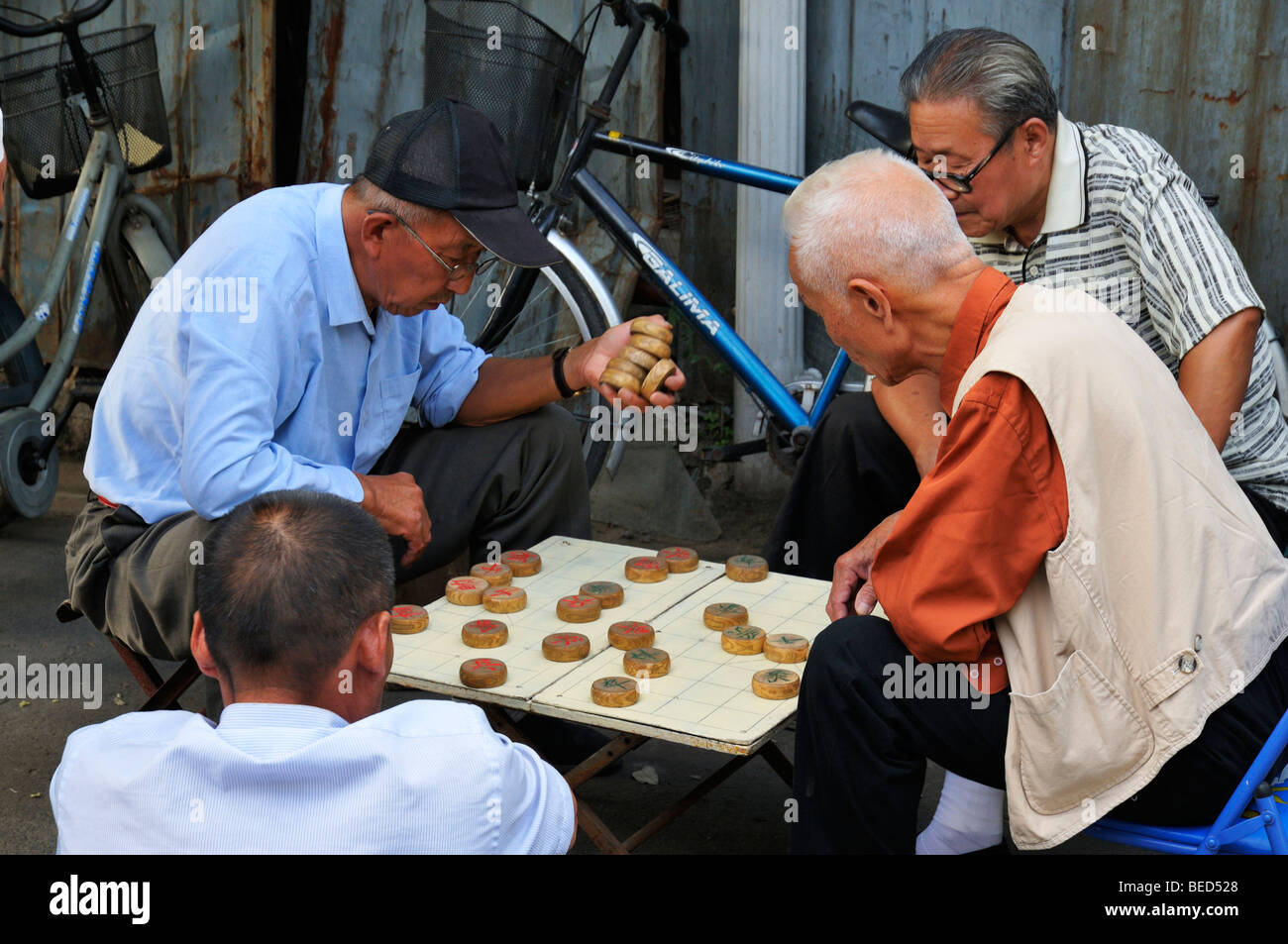 Men playing Chinese Chess in a Hutong street, Beijing CN Stock Photo