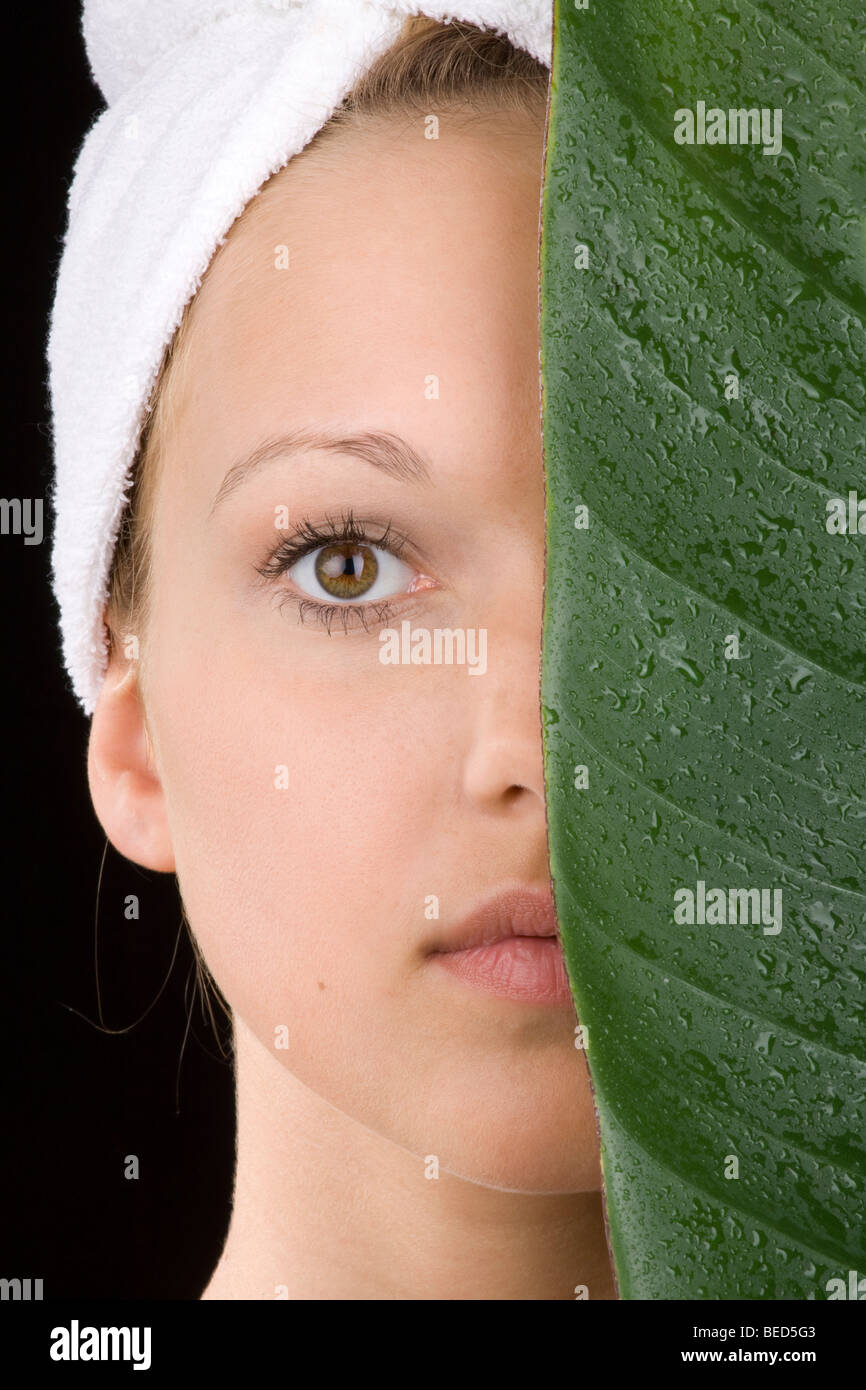 Young woman, moisture and sensitive skin, leaf covered with waterdrops - Stock Image
