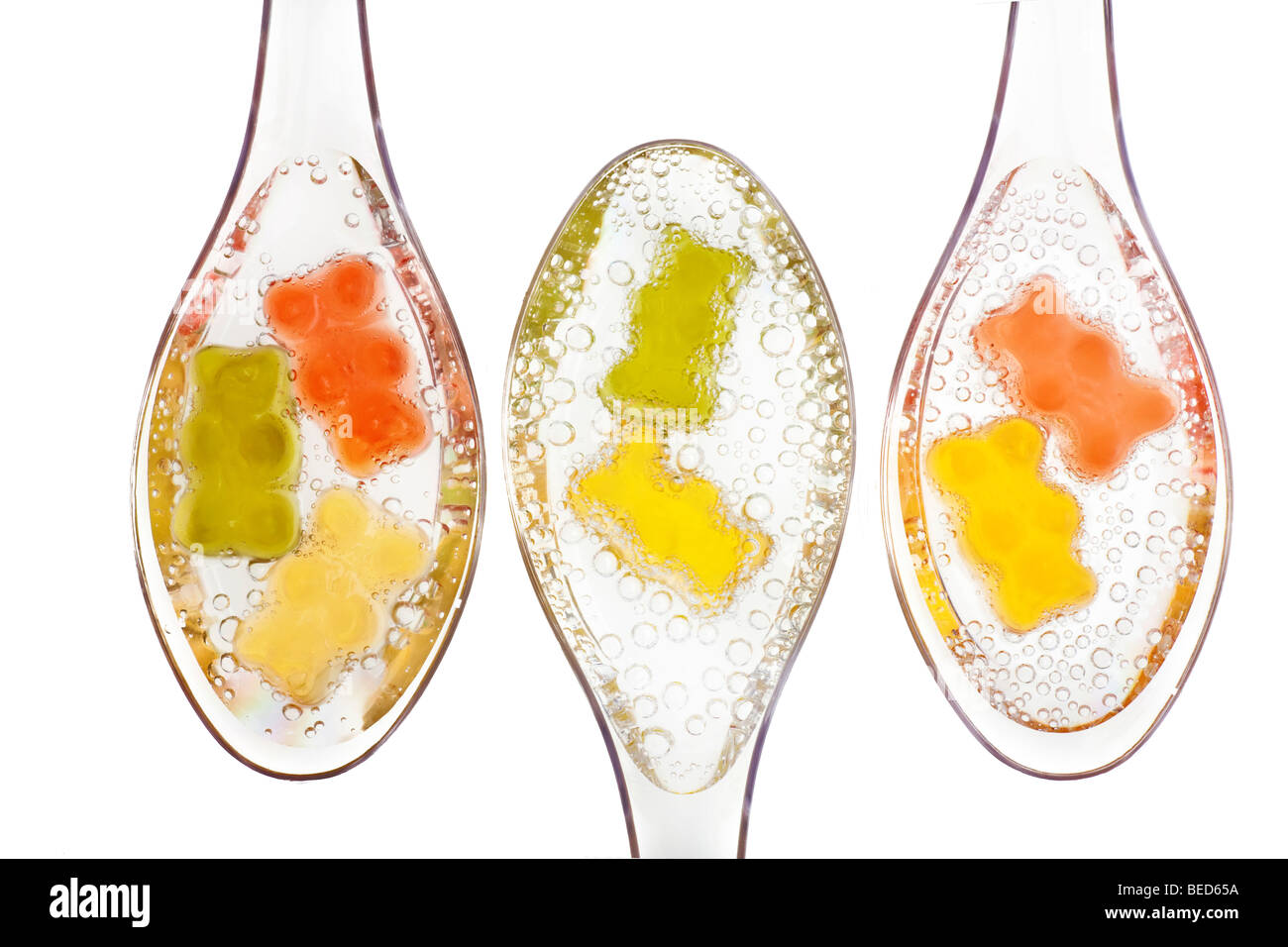 Gummi Bears in water on transparent spoons Stock Photo