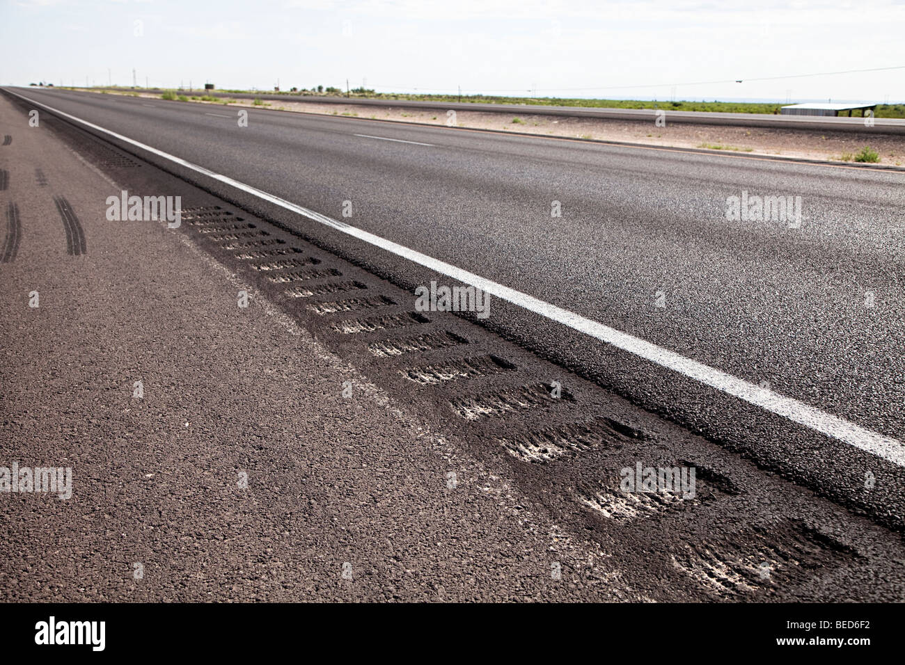 Rumble strip to cause vibration in wheels if vehicle crosses the line at the edge of the road Carlsbad New Mexico Stock Photo