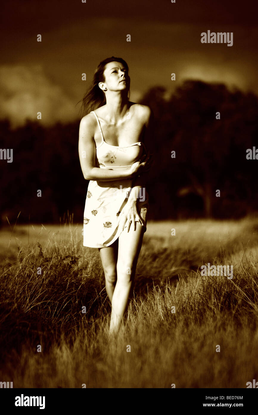 Woman wearing a light summer dress, walking barefooted through a field, looking anxious, imminent thunder clouds - Stock Image