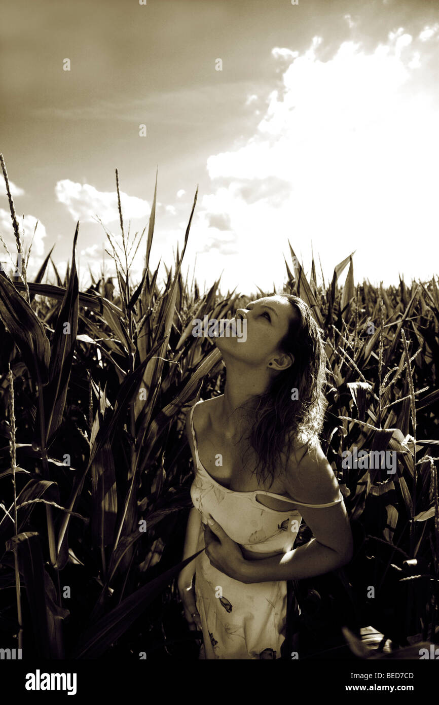 Woman wearing a light summer dress in a corn field, summerly stormy atmosphere Stock Photo
