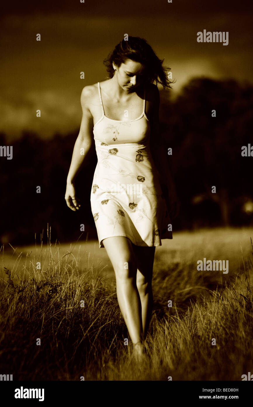 Woman wearing a light summer dress, walking barefooted through a field, imminent thunder clouds in the back - Stock Image