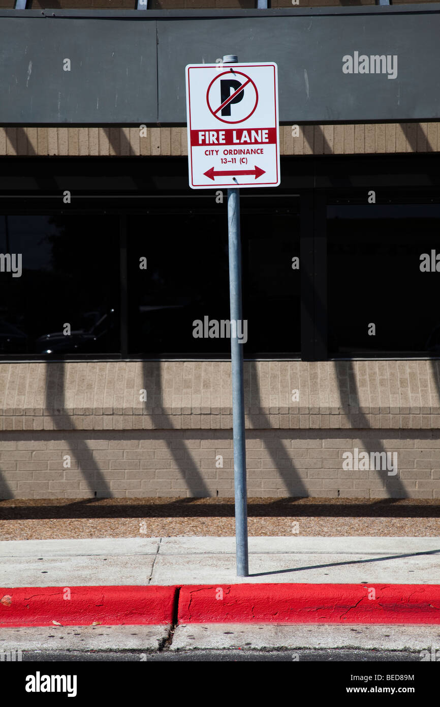Fire lane sign with no parking and red line on sidewalk Houston Texas USA - Stock Image