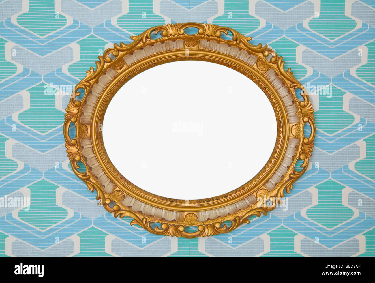 Kitschy golden plastic oval frame, horizontal, mounted on wallpaper from the 1960s or 1970s, frontal view - Stock Image