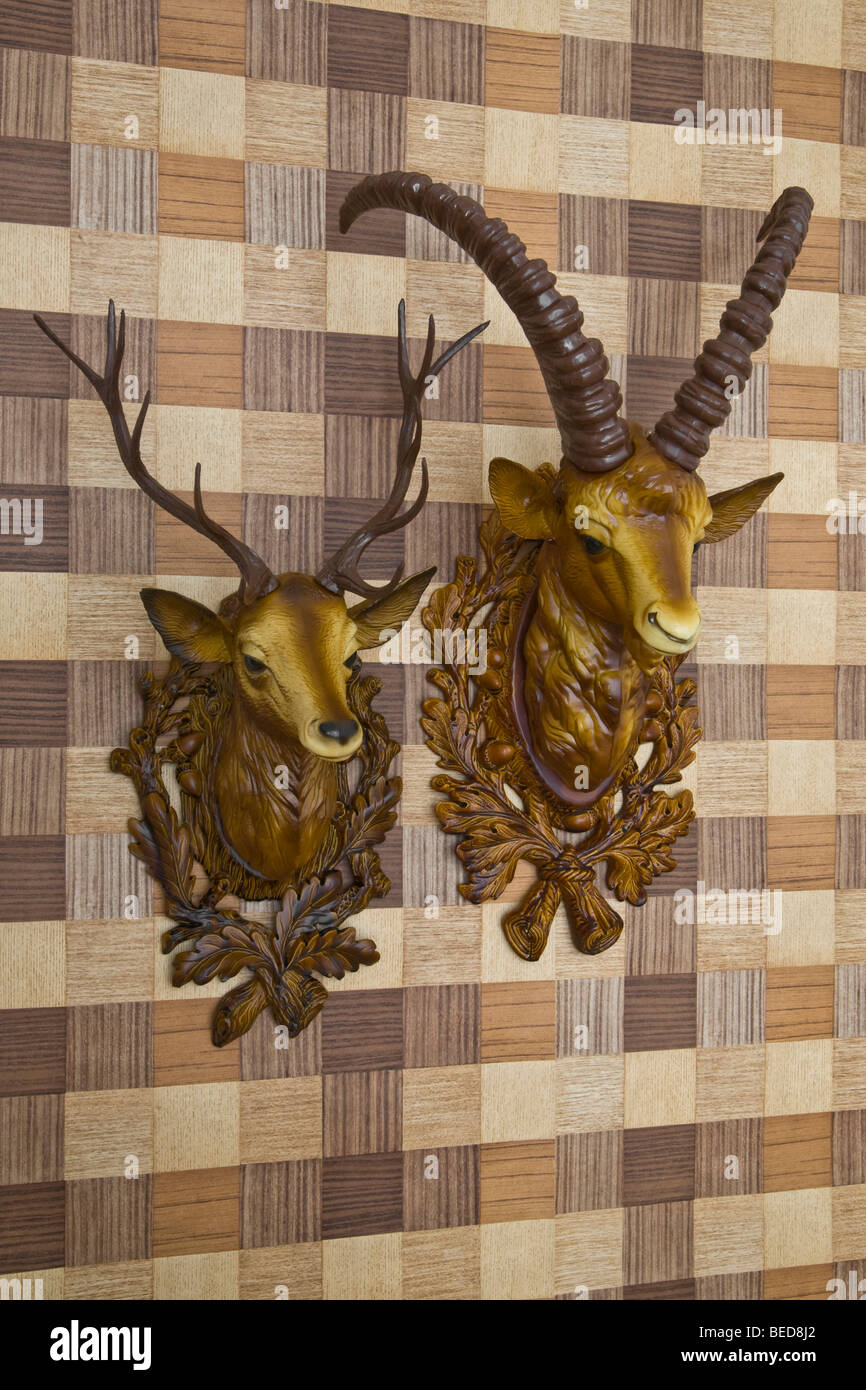 Plastic heads of an ibex and a deer mounted on imitation wood wallpaper, side view - Stock Image