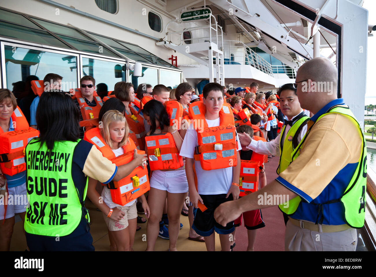 Cruise passengers are led through a muster station drill before ship leaves port. - Stock Image