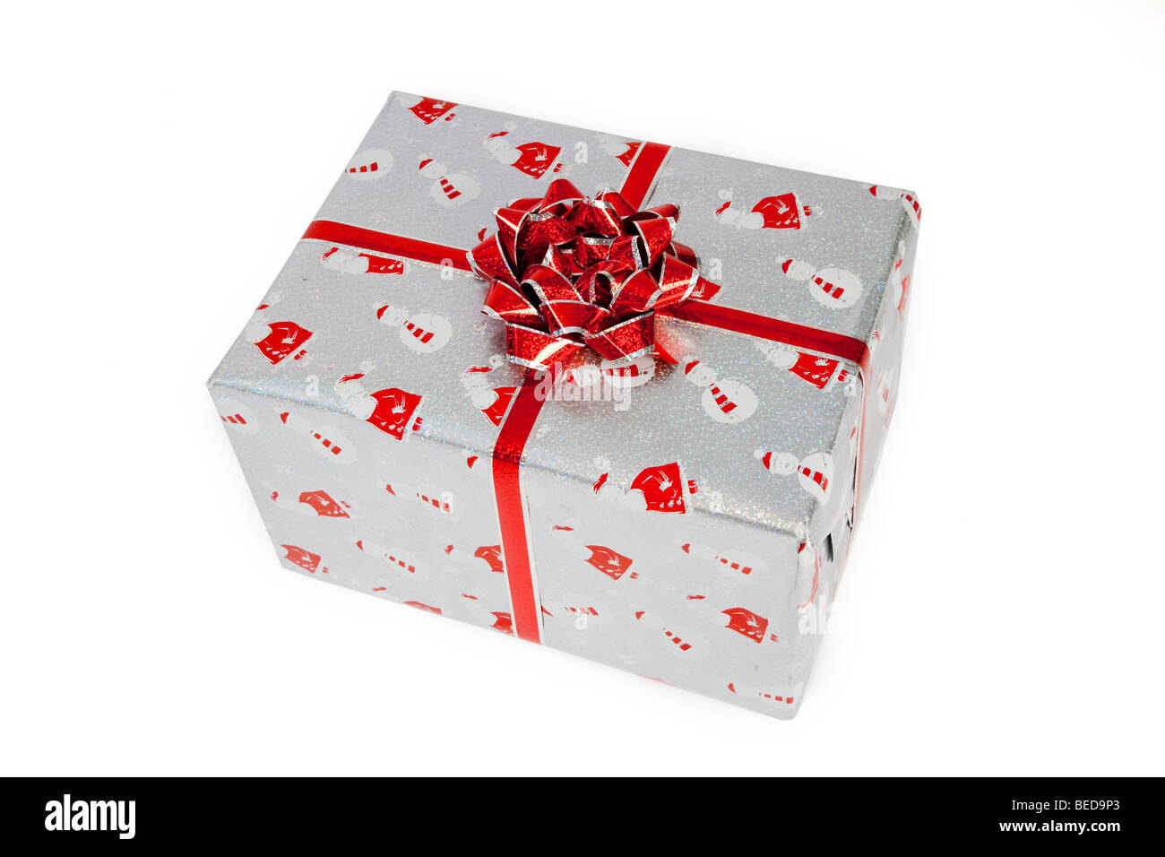 Christmas present,  wrapped with a red bow and santa and snowman paper - Stock Image