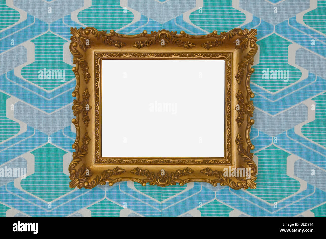 Rectangular golden plastic frame, mounted on out-dated wallpaper from the 1960s or 1970s - Stock Image