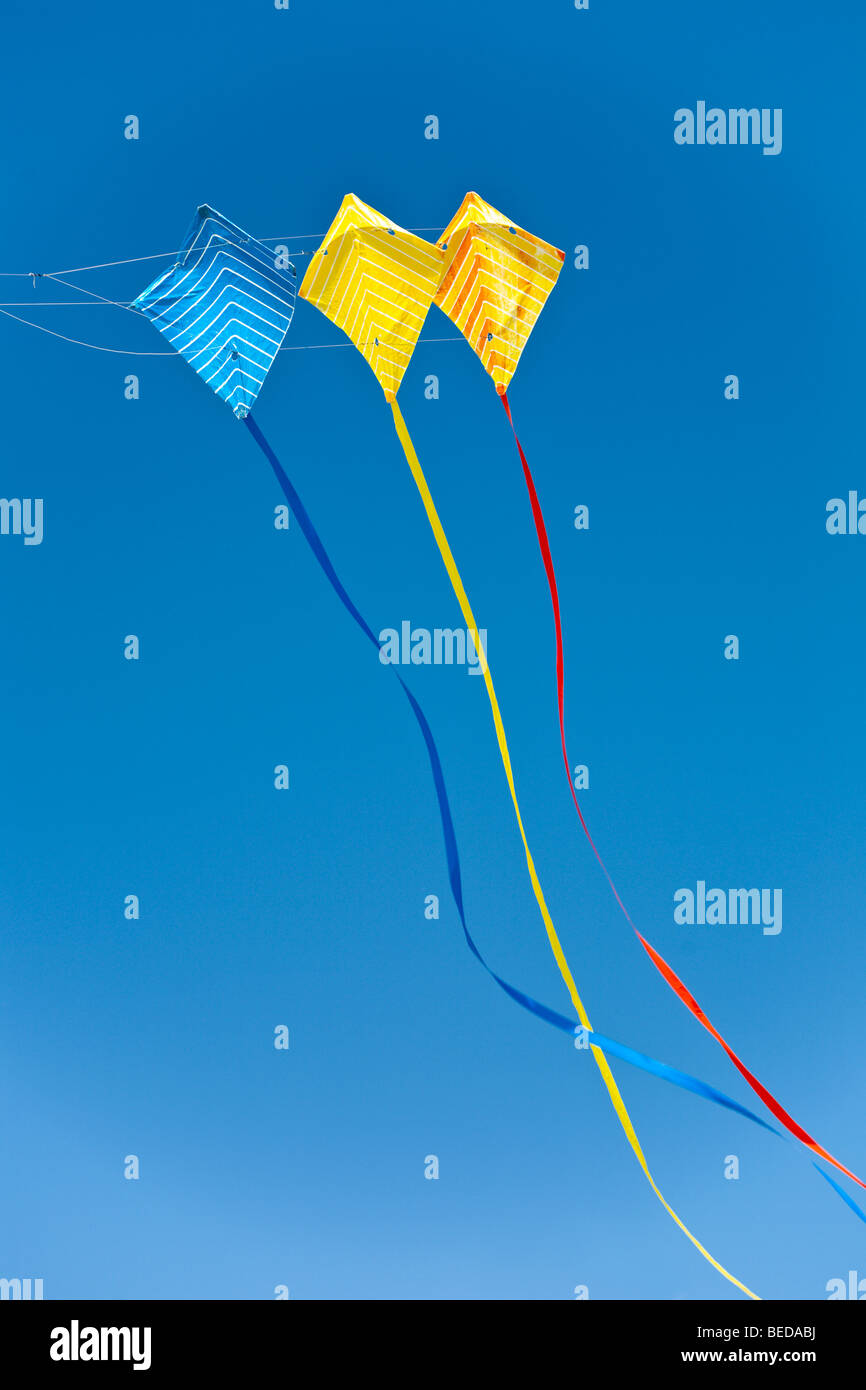 Triple multi-colored kite with long tails flying in deep blue sky. - Stock Image