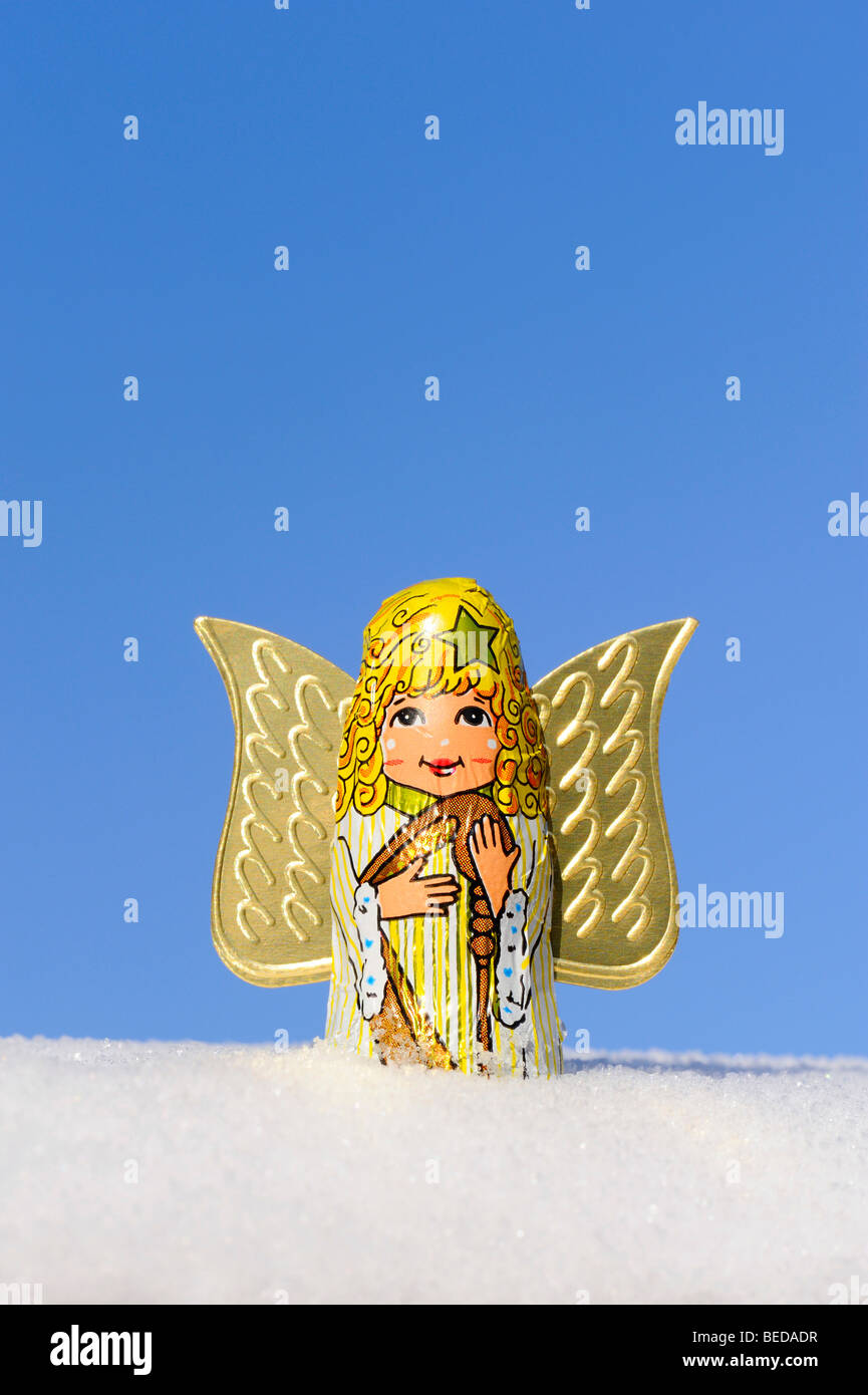 Angel in snow against blue sky - Stock Image