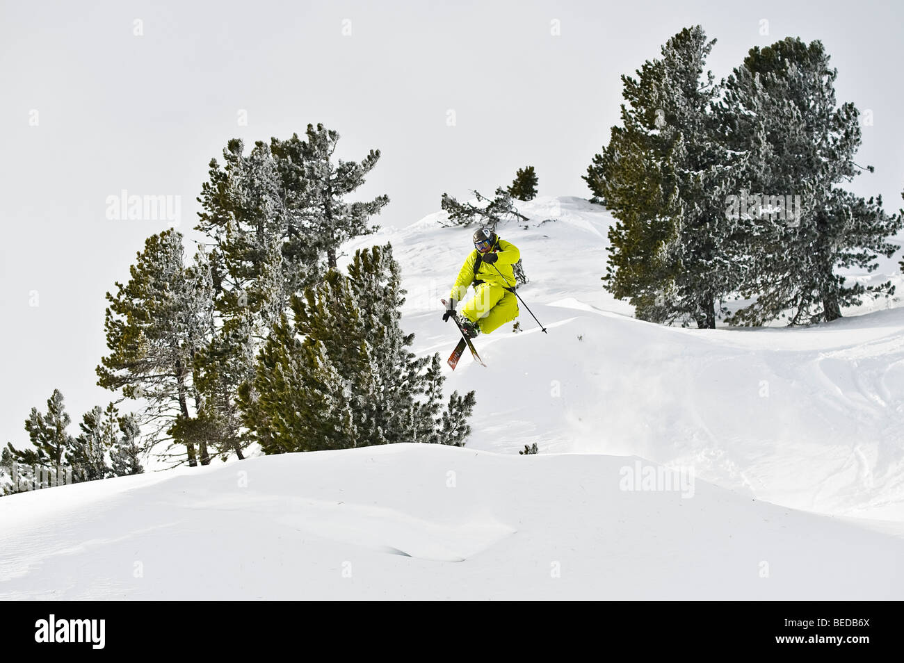 Deep snow skier, freerider, jumping, tail grab, over a snowdrift - Stock Image
