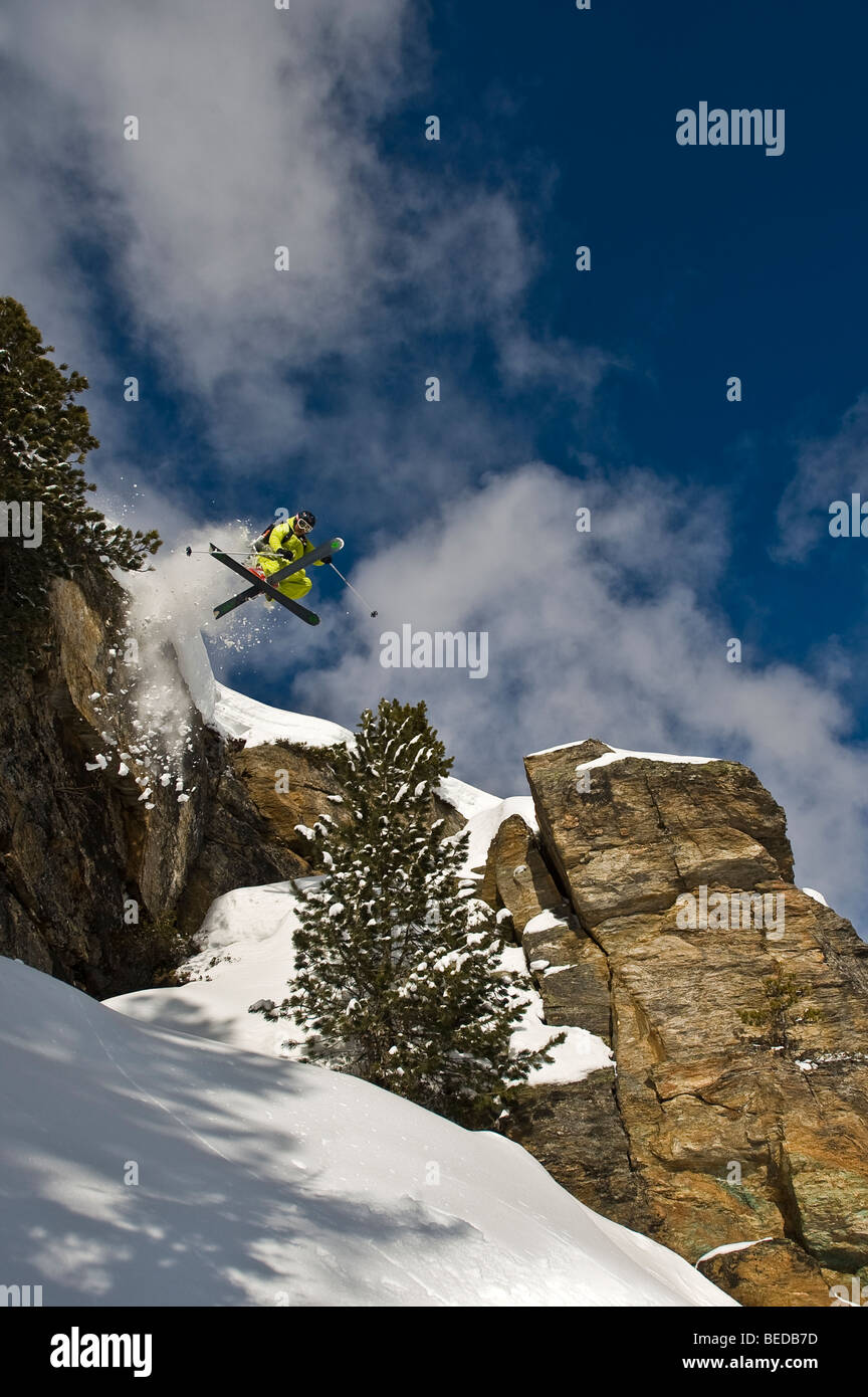 Deep snow skier, freerider, jumping, twist, over a rock wall with crossed skis - Stock Image