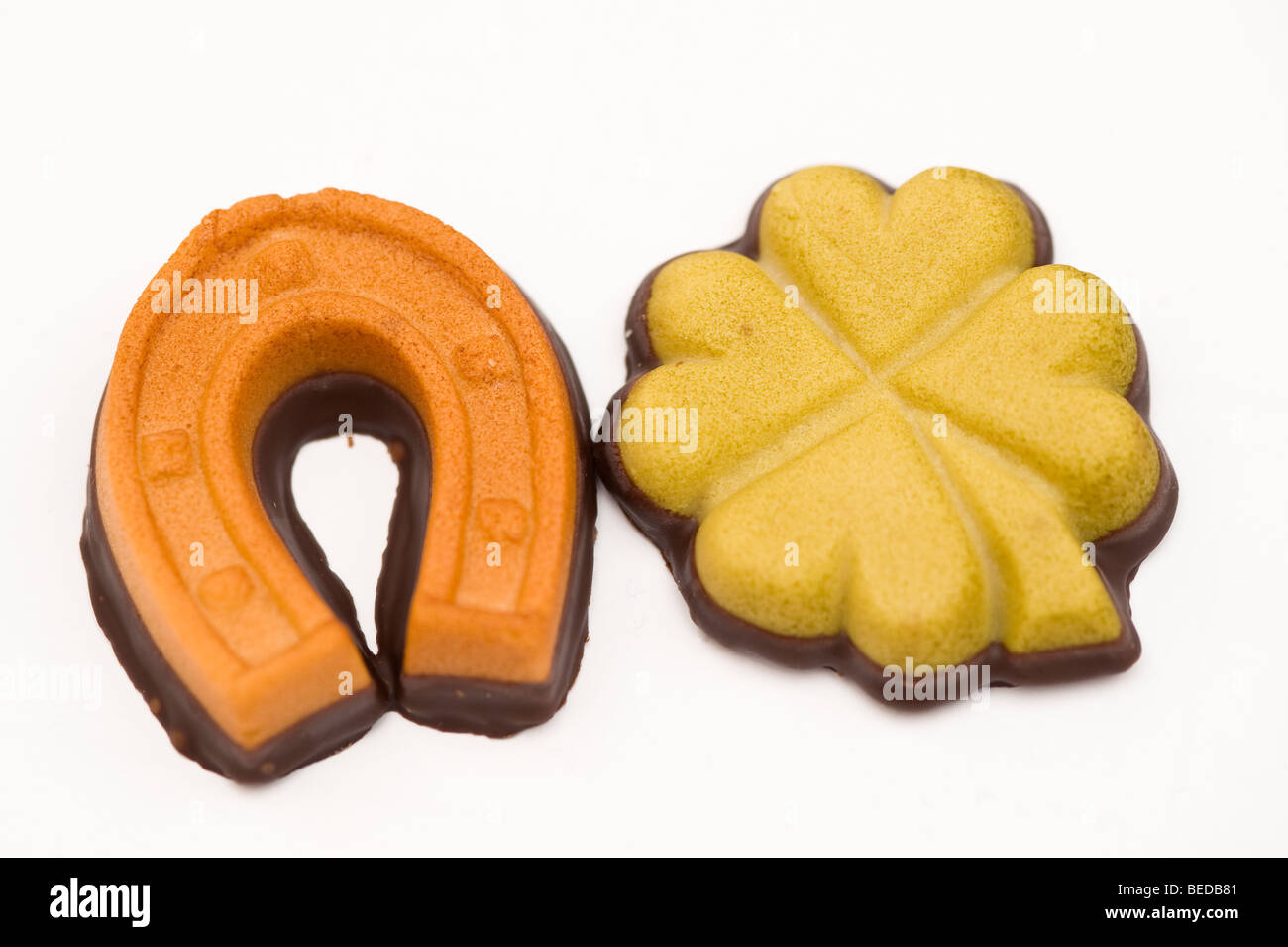 Good luck charms made of marzipan, horseshoe and cloverleaf - Stock Image