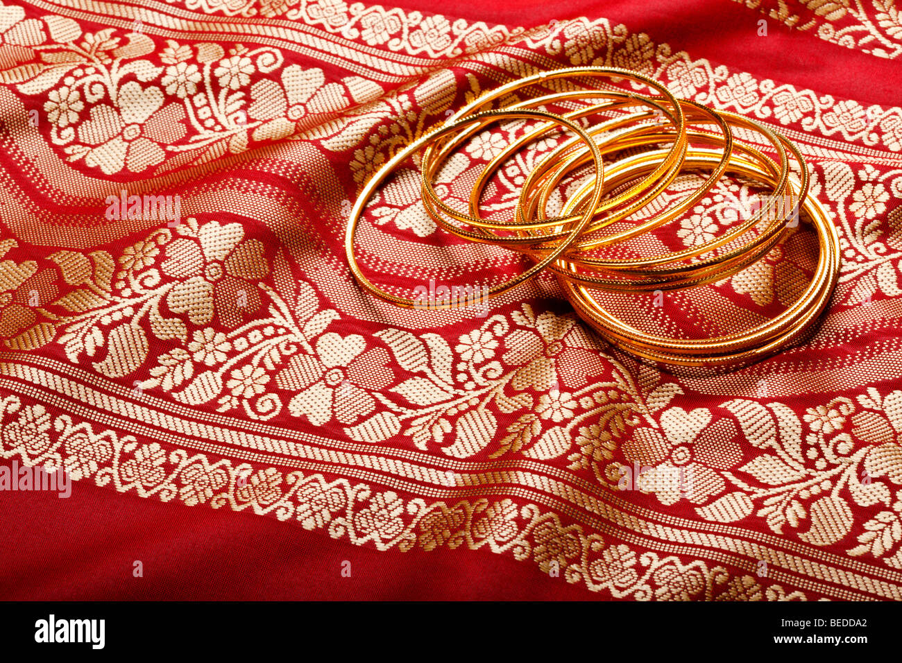 Indian sari with golden bangles close up - Stock Image