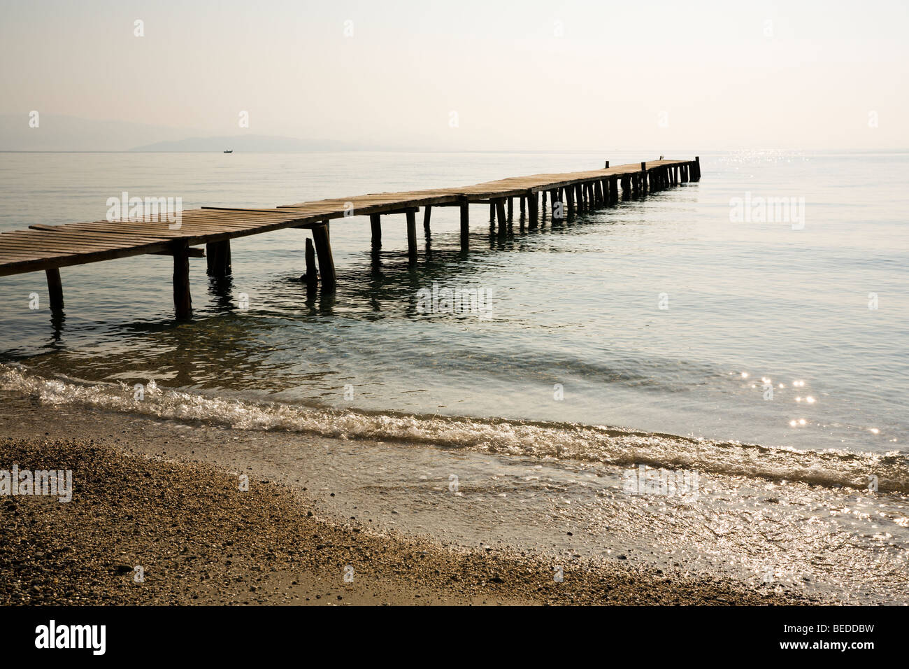 wooden jetty at the beach of Ipsos, Corfu, Greece, in the morning - Stock Image