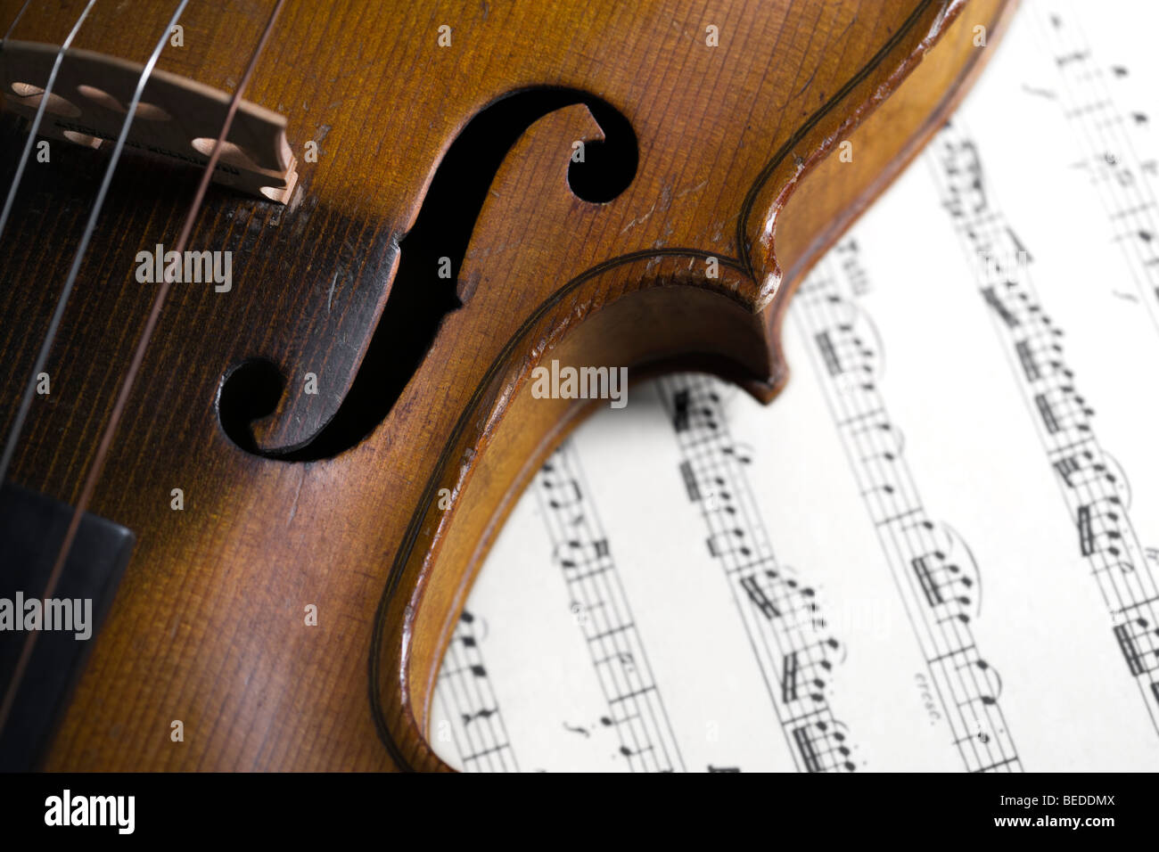 closeup of old violin on sheet music by Mozart Stock Photo