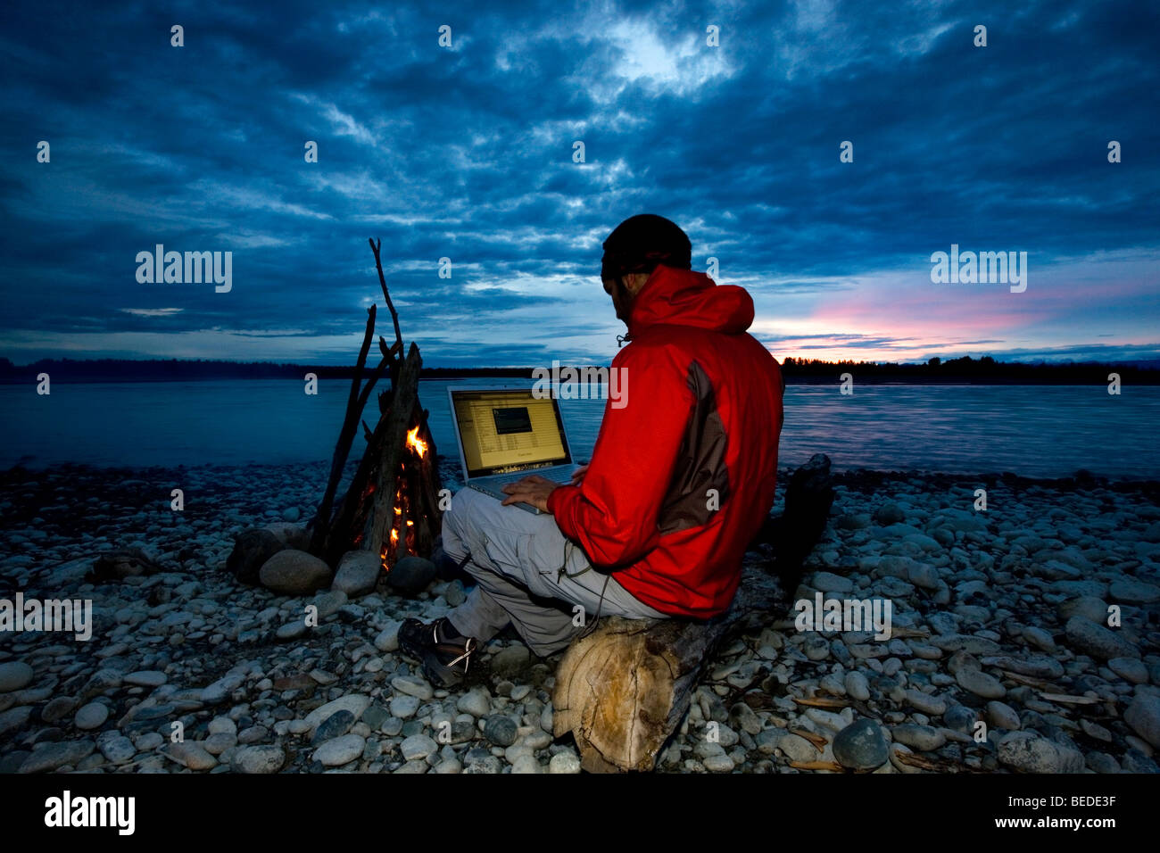 Nature photographer at work in the evening next to a campfire, Alaska, USA, North America Stock Photo