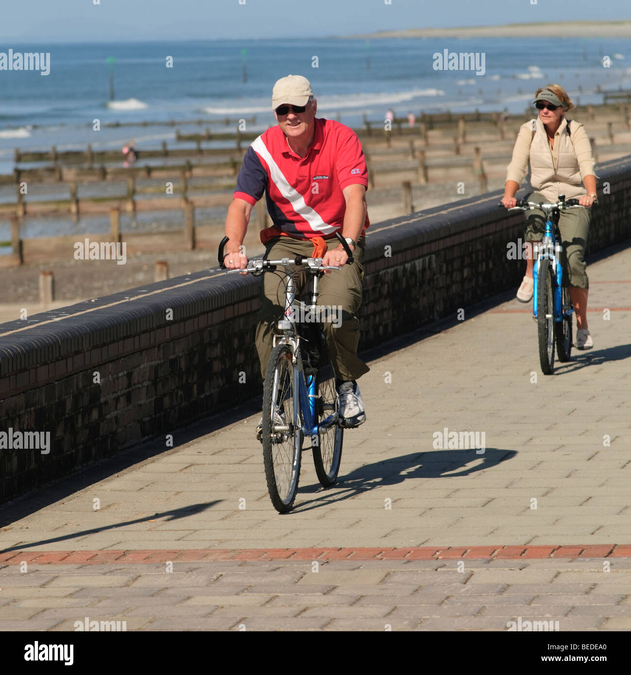 A couple cycling on their bikes along the seaside  promenade at Tywyn Gwynedd north wales UK - Stock Image