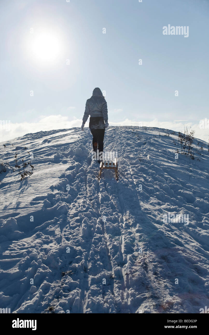 Young woman pulling a sledge in the snow - Stock Image
