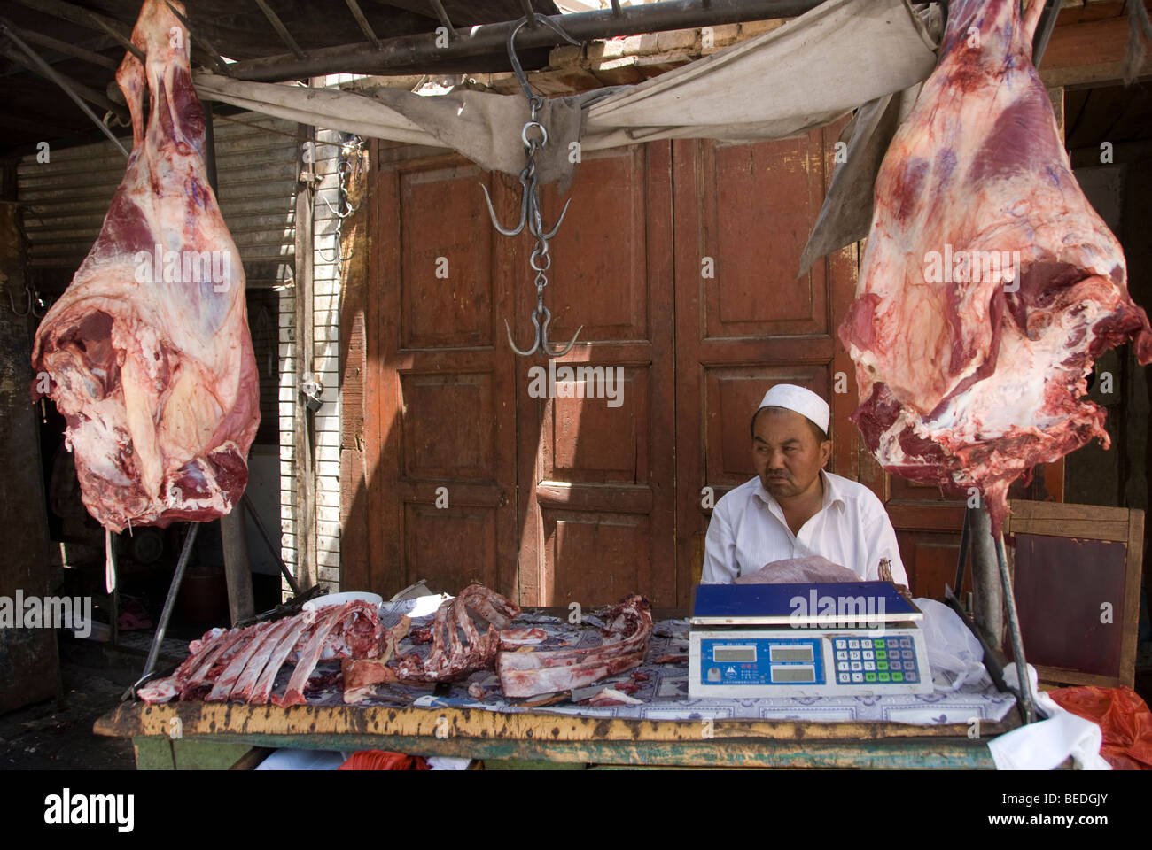 Local Butcher selling meat in the middle of a market in Kashgar, Xinjiang Province, China 2008 - Stock Image