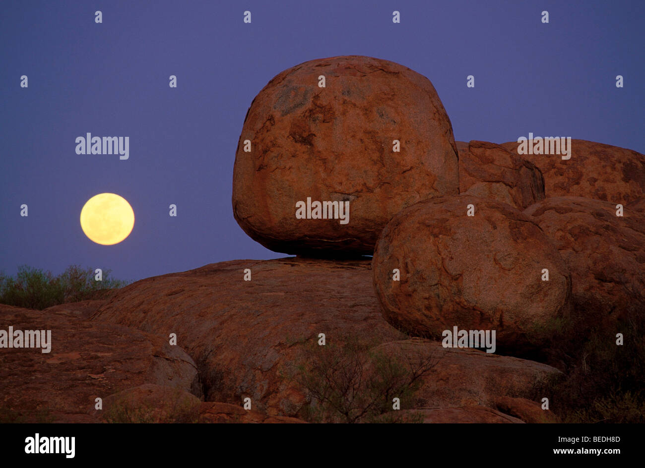 Full moon behind round boulders, Devils Marbles Conservation Reserve, Northern Territory, Australia Stock Photo