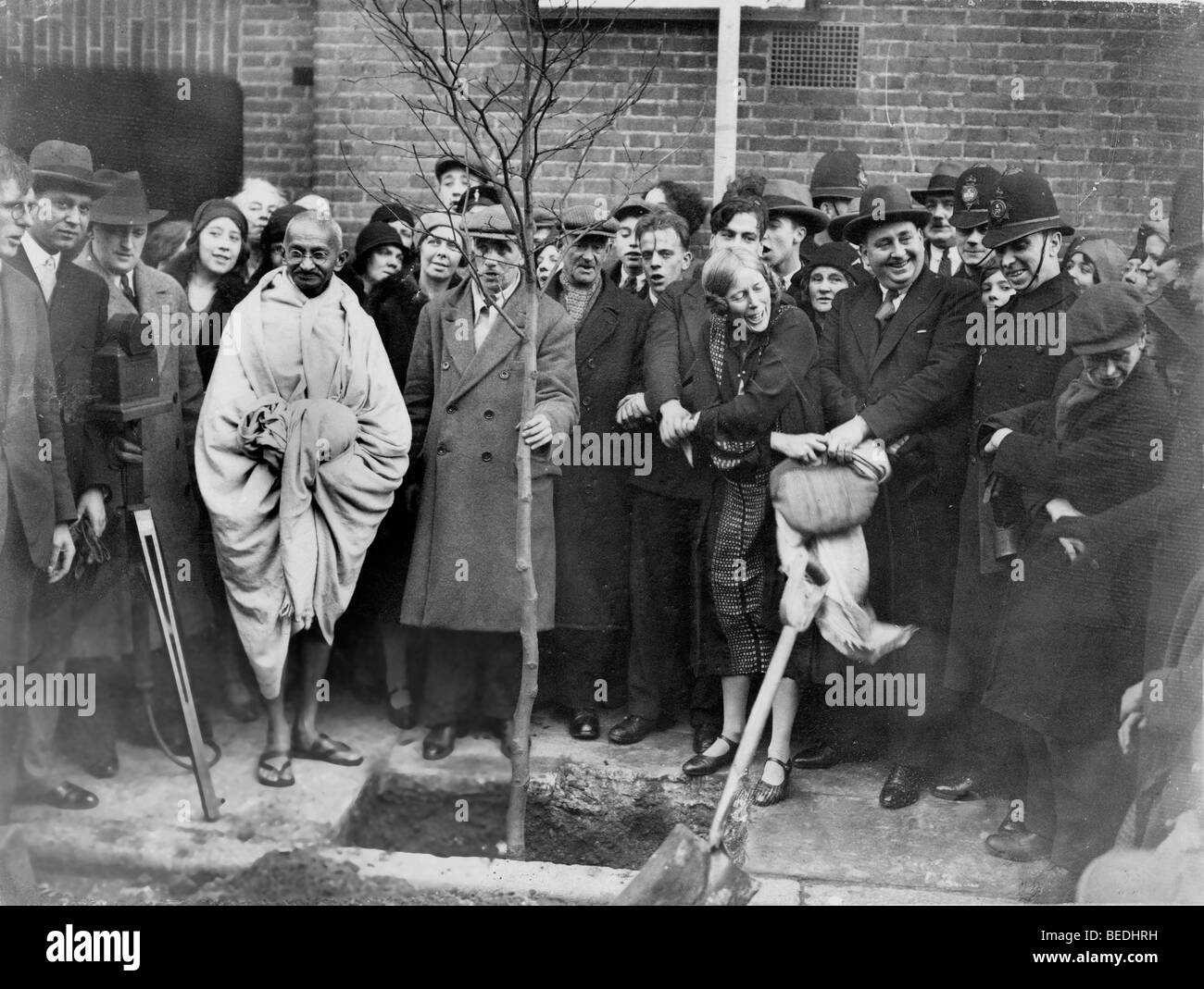 As a token of thanks, MAHATMA GANDHI, second left from tree, planted a tree outside Kingsley Hall in London on December - Stock Image