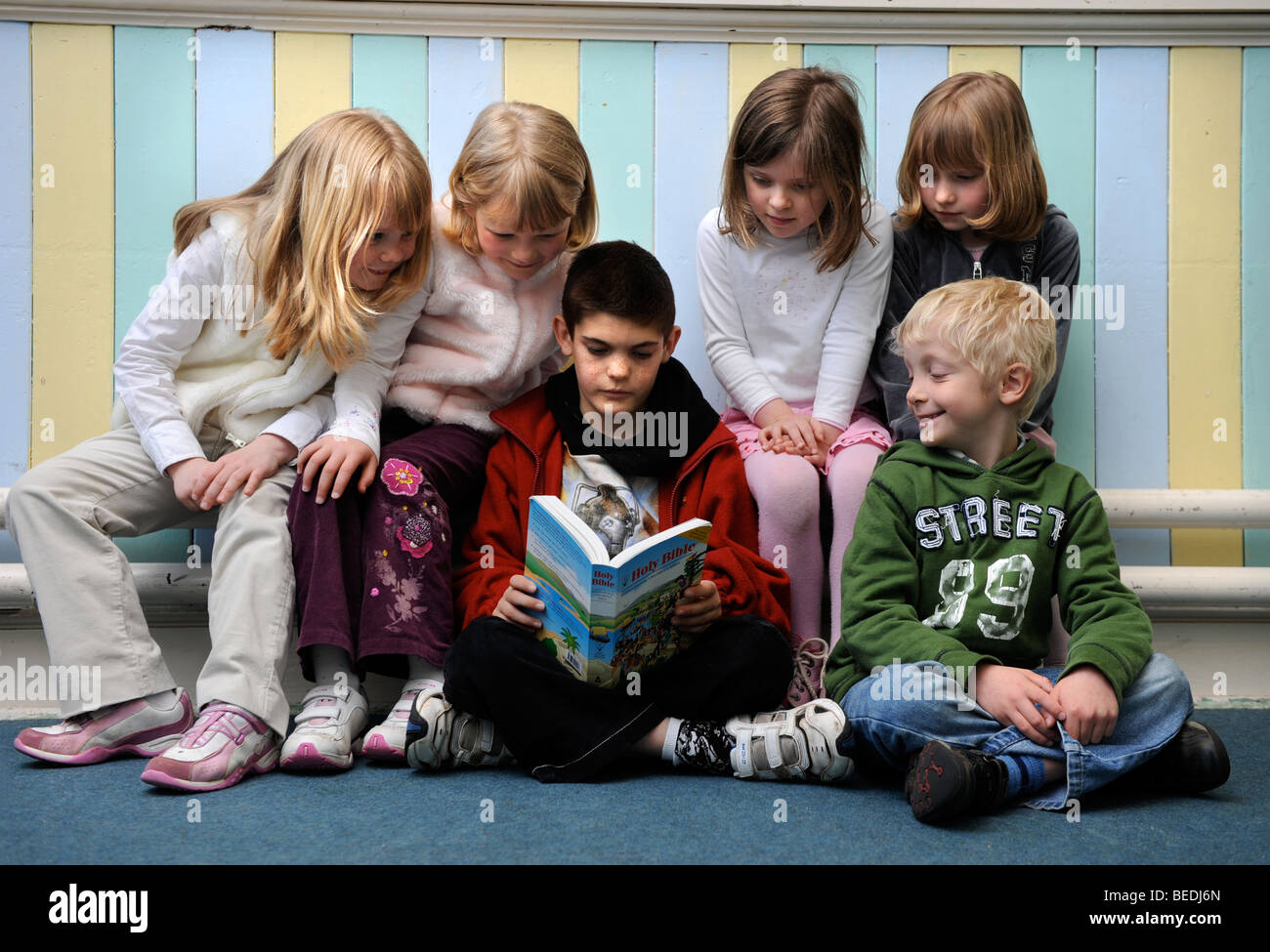 A GROUP OF FOUR GIRLS AND TWO BOYS READING A BIBLE TOGETHER AT A SUNDAY SCHOOL UK - Stock Image