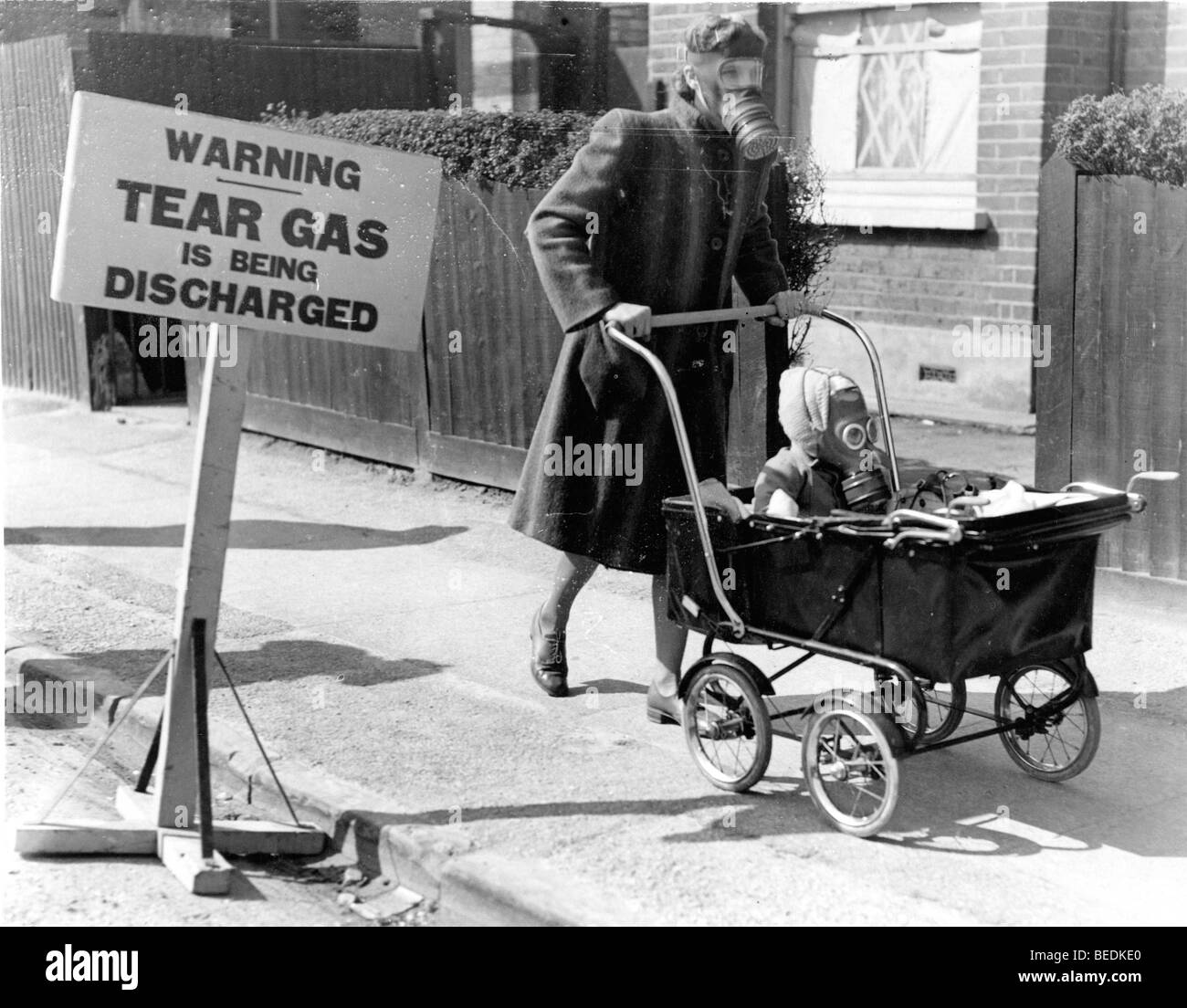 A Mother Pushes Her Baby In A Stroller Wearing Gas Masks