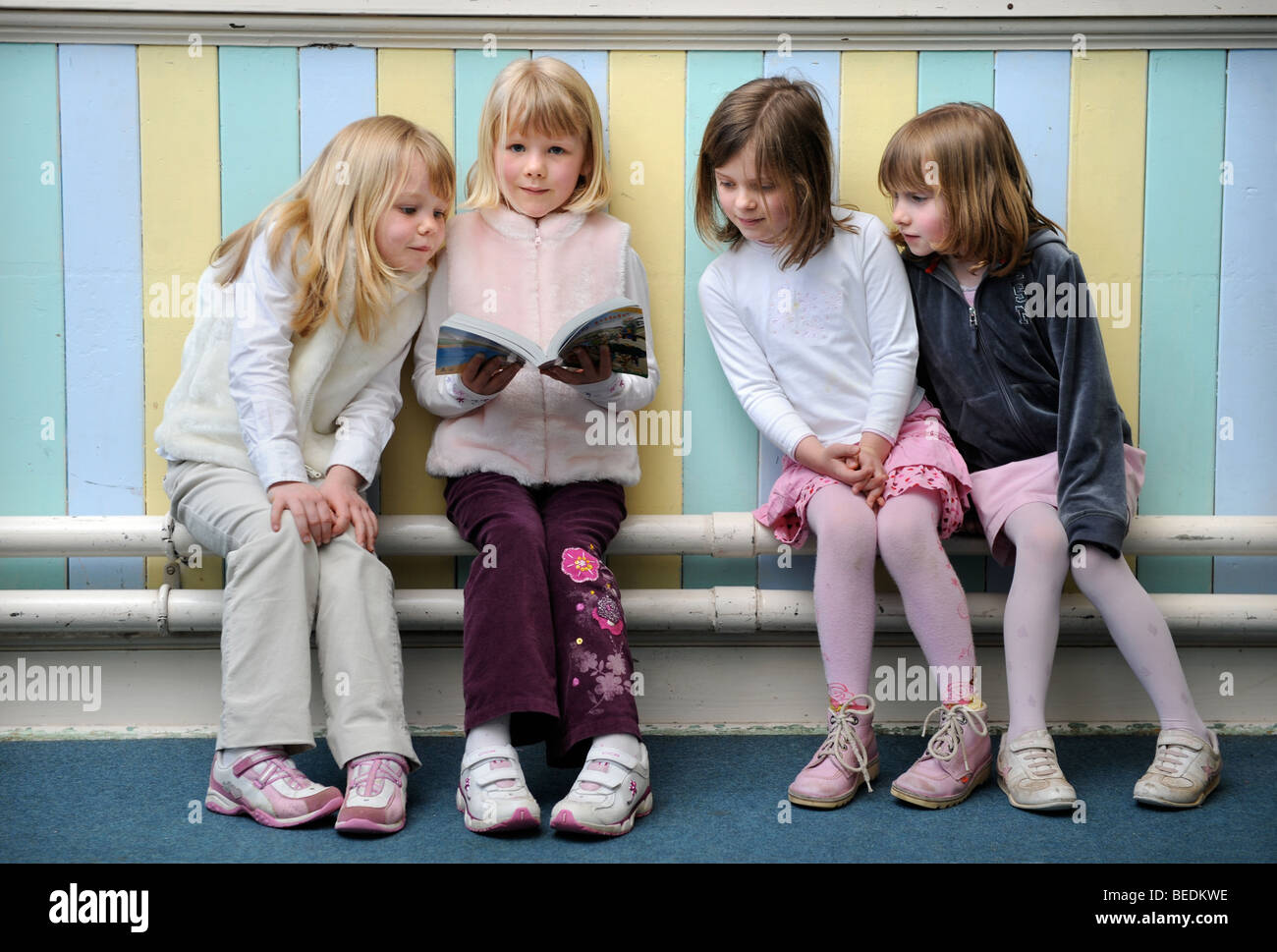 A GROUP OF FOUR GIRLS READING A BIBLE TOGETHER AT A SUNDAY SCHOOL UK - Stock Image