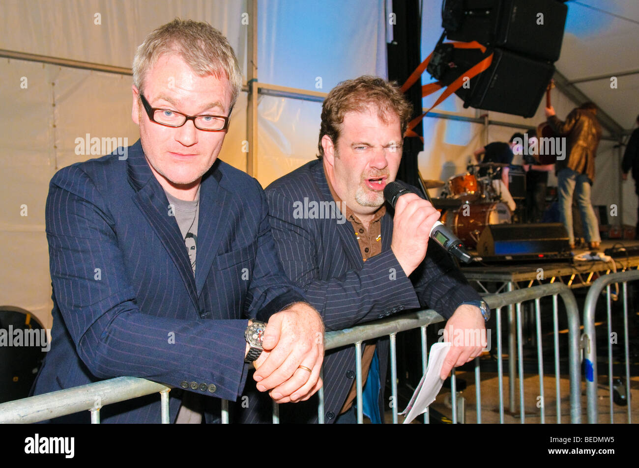 Conor Grimes (l) and Alan McKee (r), Northern Ireland actors, writers, comedians and presenters,  at a concert. - Stock Image