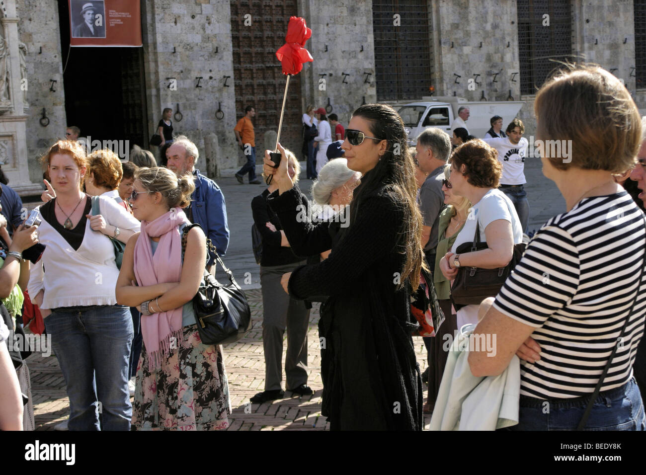 Travel guide with red umbrella for orientation, surrounded by tourists on Campo of Siena, Tuscany, Italy - Stock Image