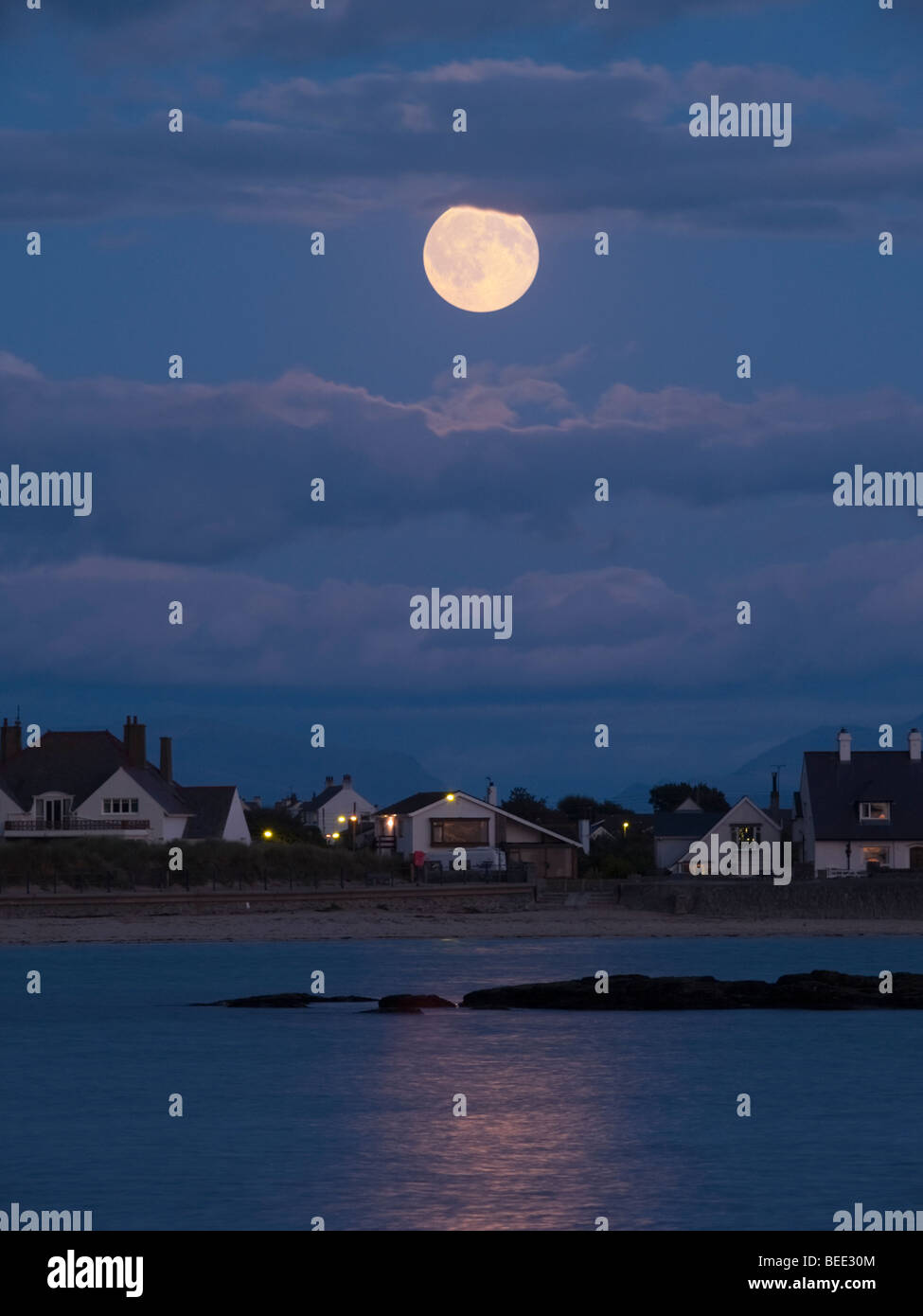 Trearddur, Anglesey, North Wales, UK. MOONRISE over TREARDDUR BAY with the full moon reflecting off the sea at dusk. - Stock Image