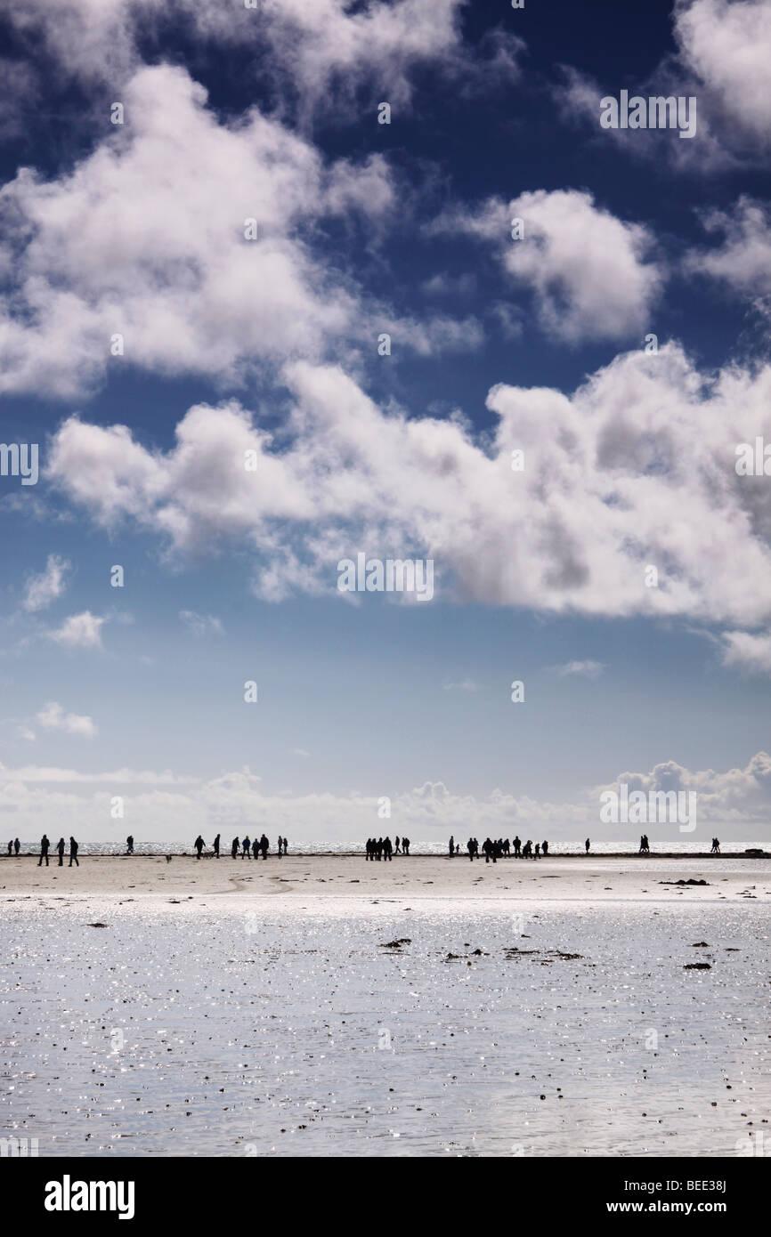 people walking along a causeway - Stock Image