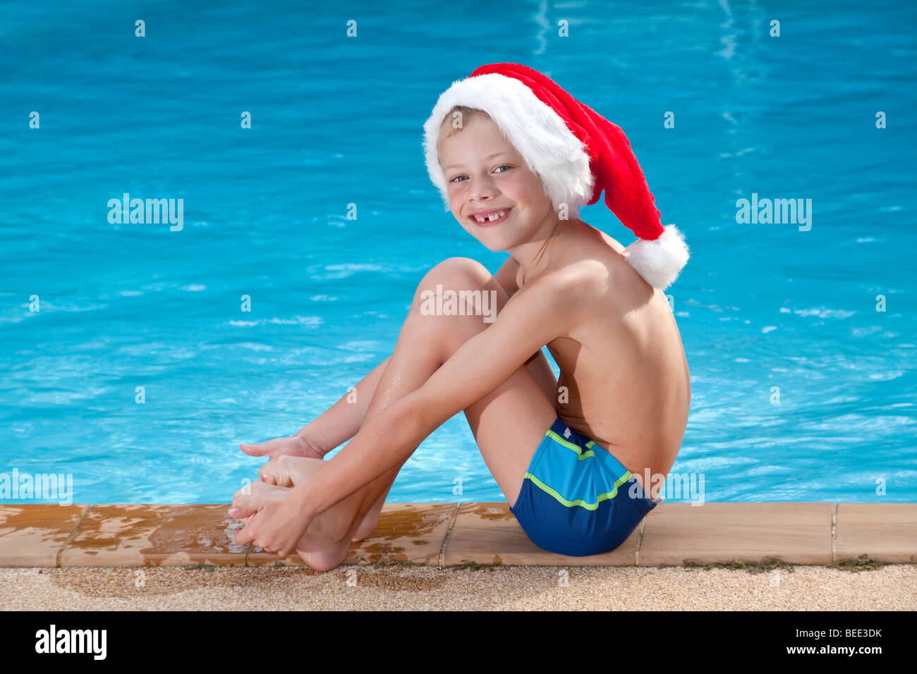 Boy wearing a Santa Clause hat sitting at a pool symbolic picture - Stock Image