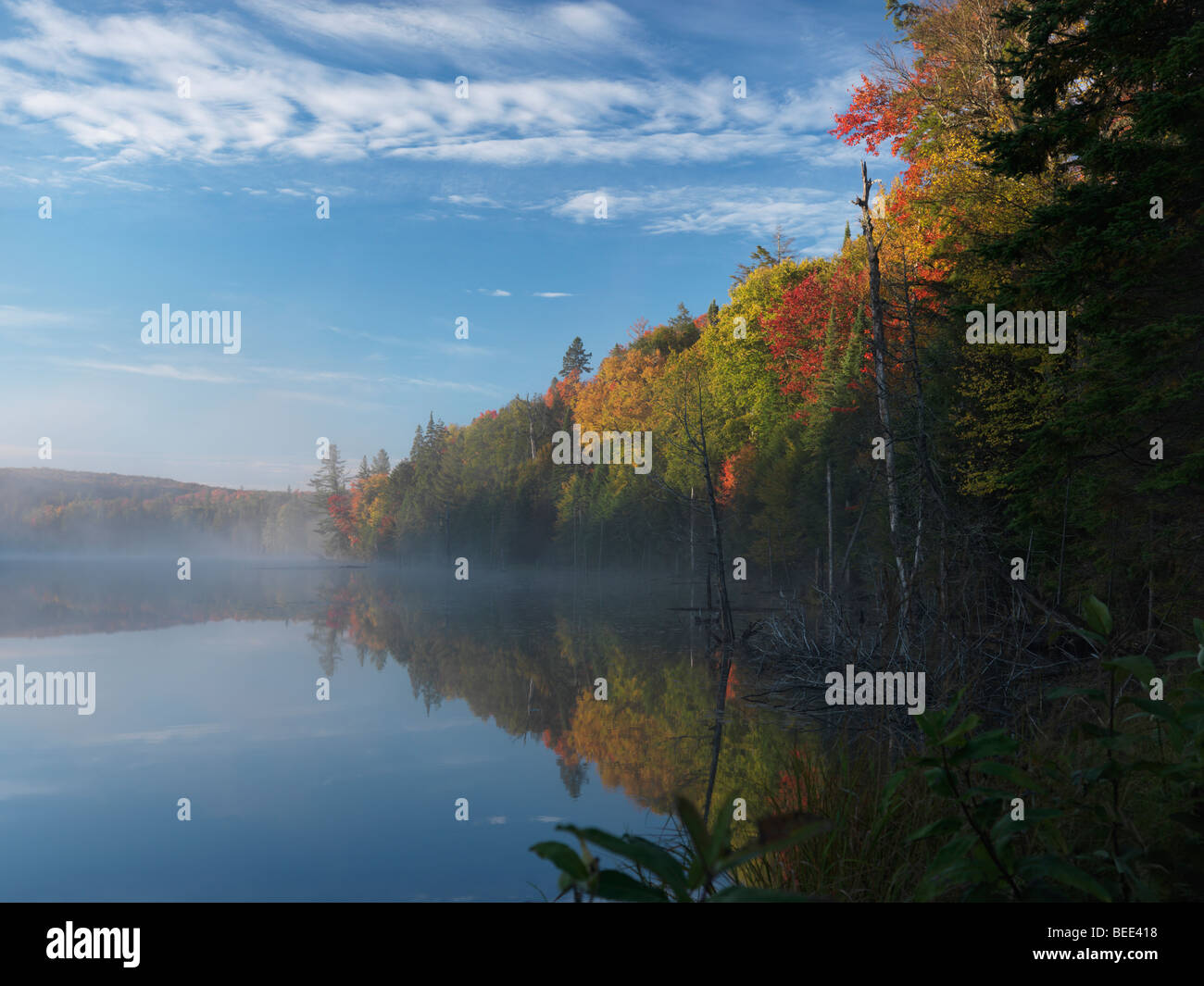 Mist over Smoke lake at dawn. Beautiful fall nature scenery - Stock Image