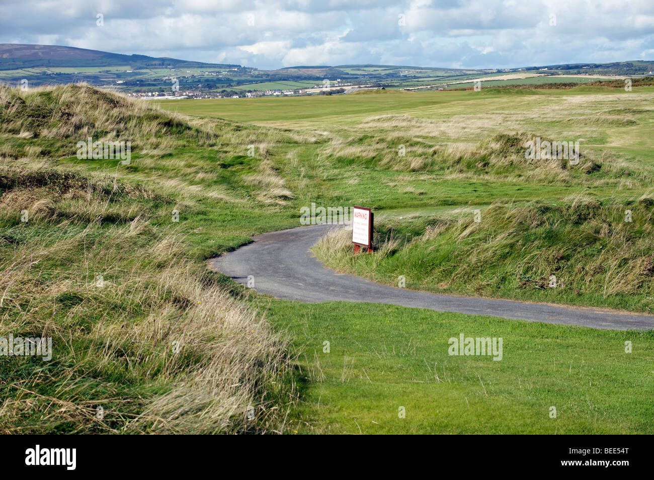 Winding path around green golf links course with background hills - Stock Image