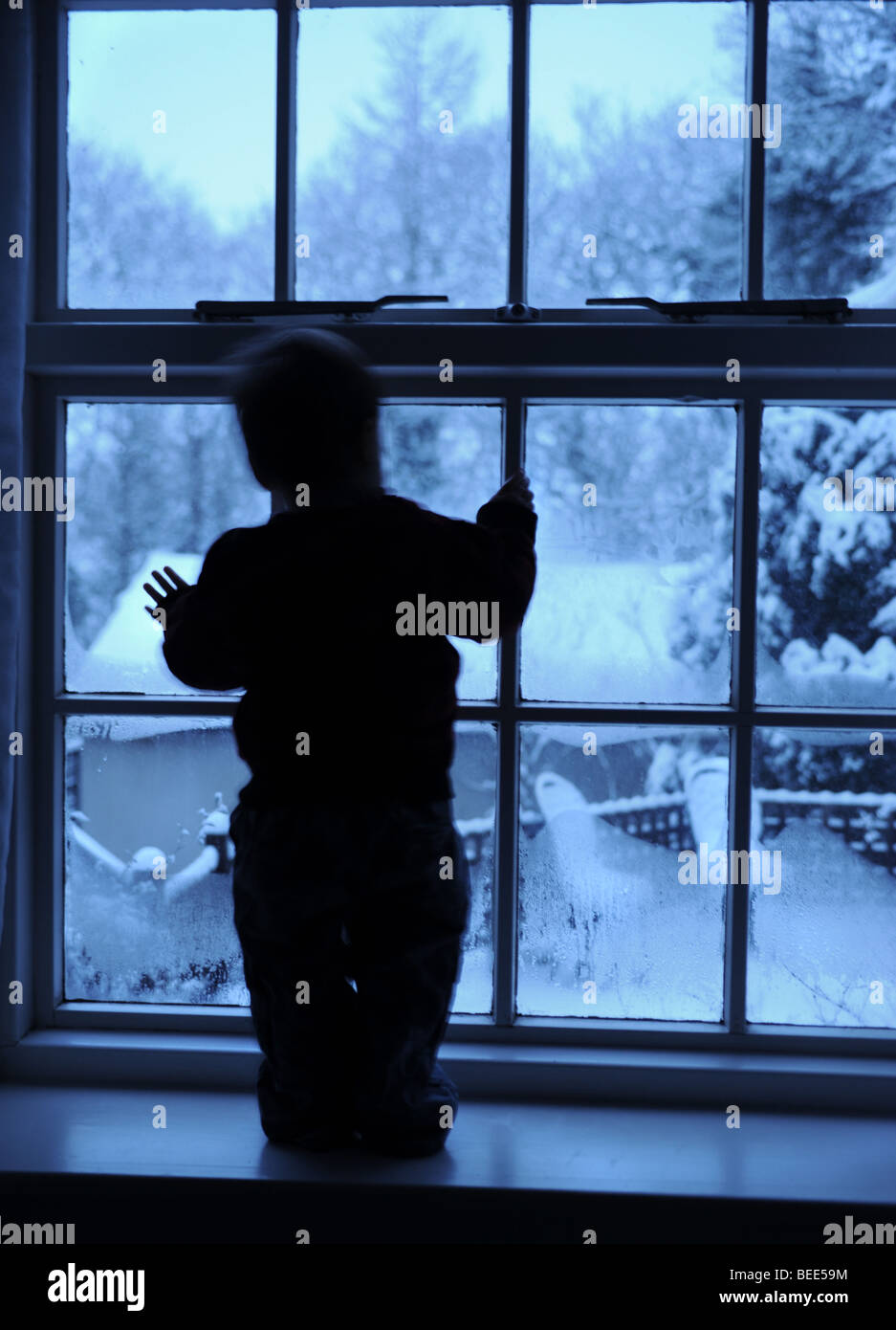 Boy in window looking at snow outside - Stock Image