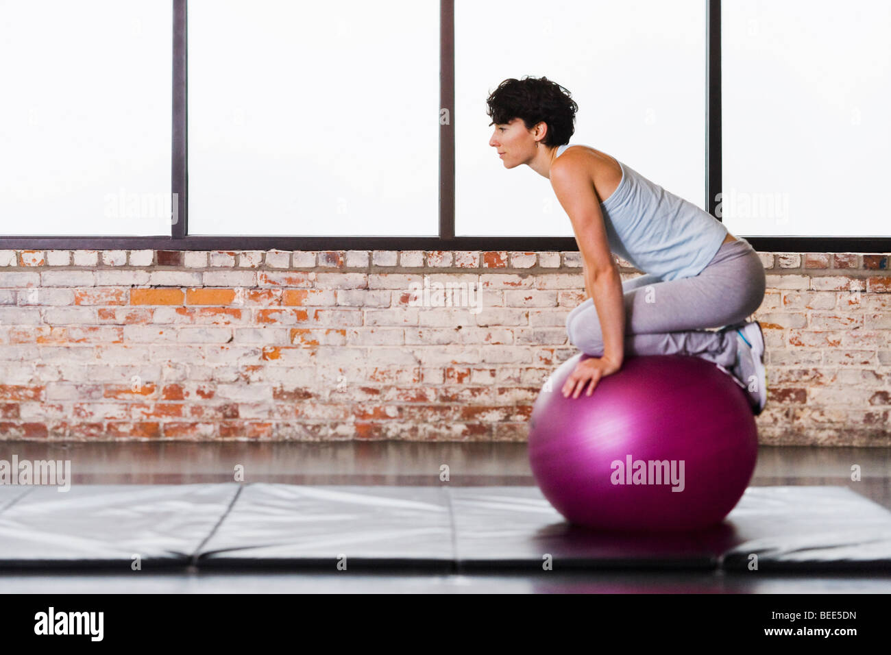 A young woman balancing atop an exercise ball while kneeling on it. - Stock Image