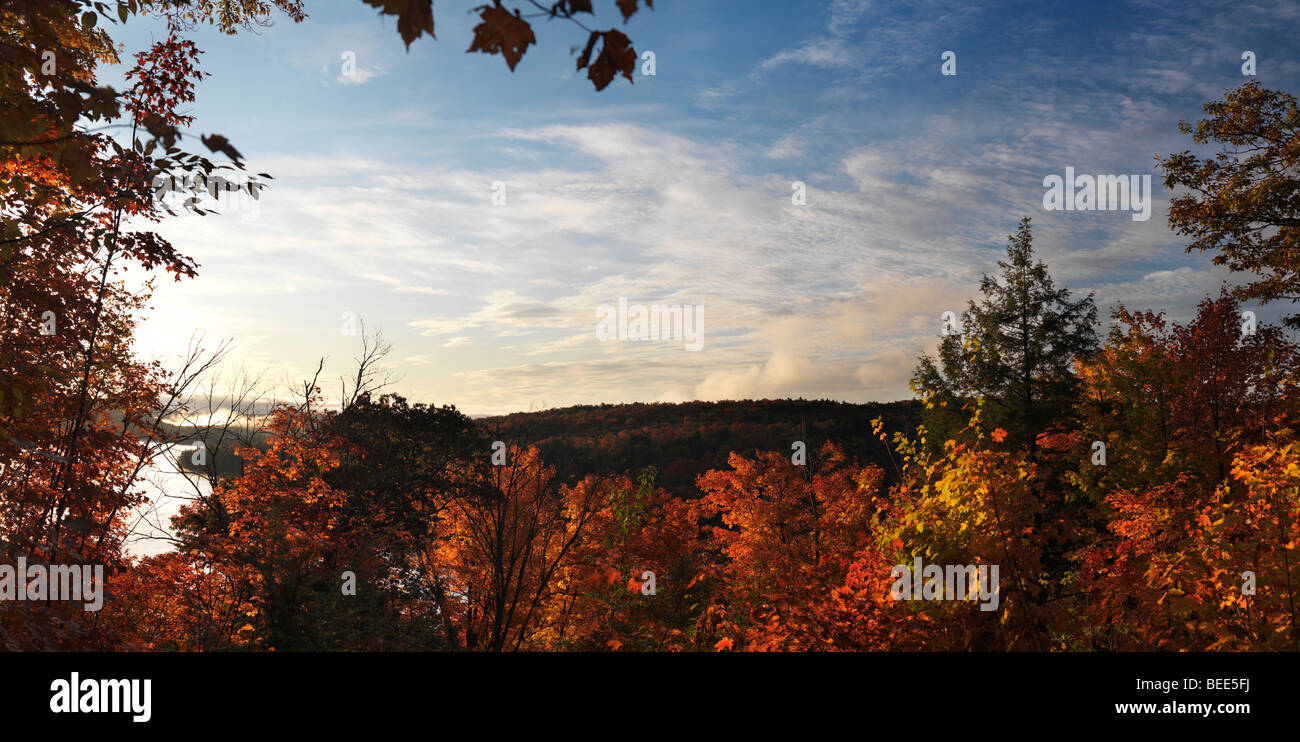 Panoramic fall nature scenery framed with colorful trees at dawn over Smoke lake - Stock Image