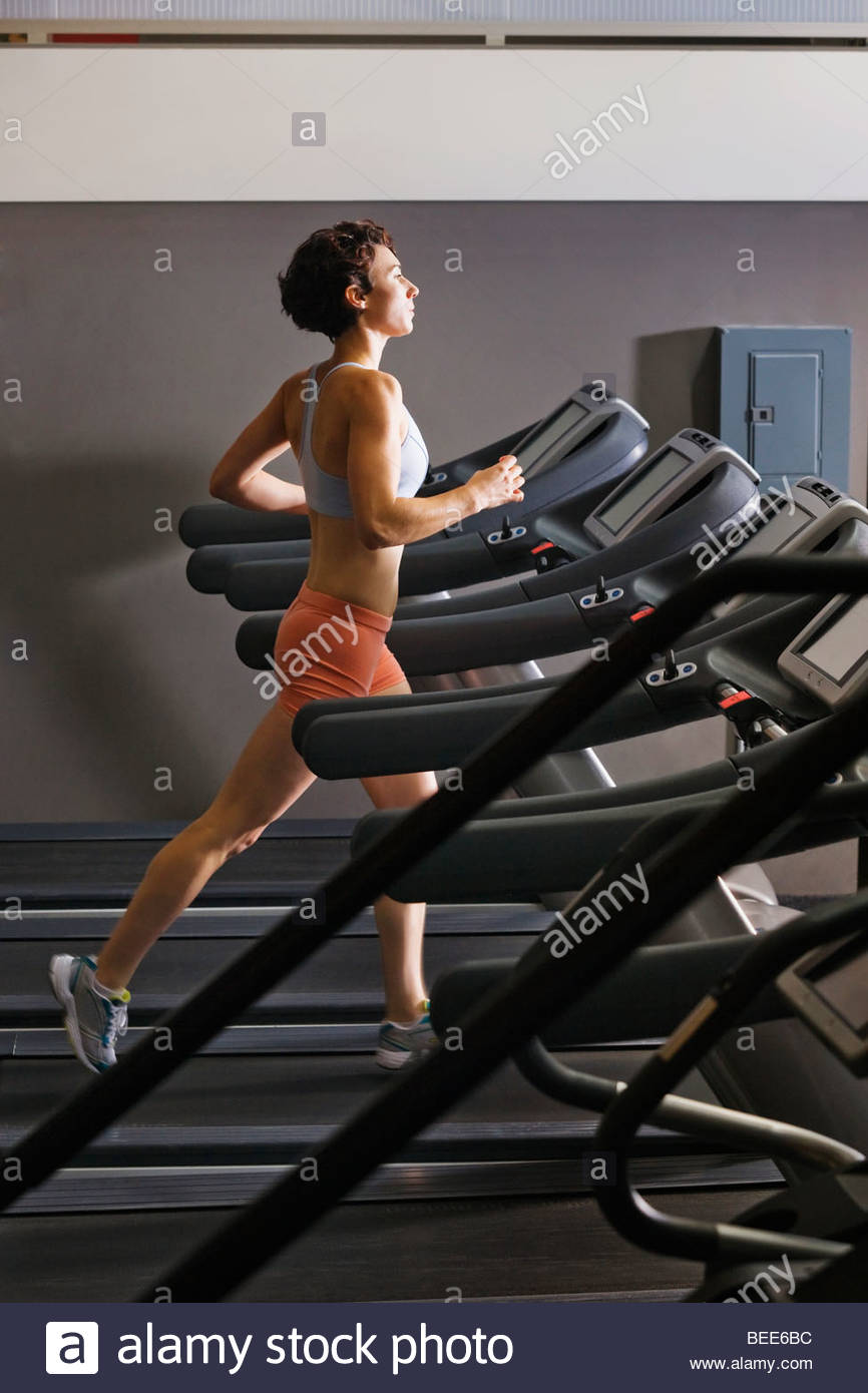 Late 20's woman running in a healthclub on a treadmill. - Stock Image