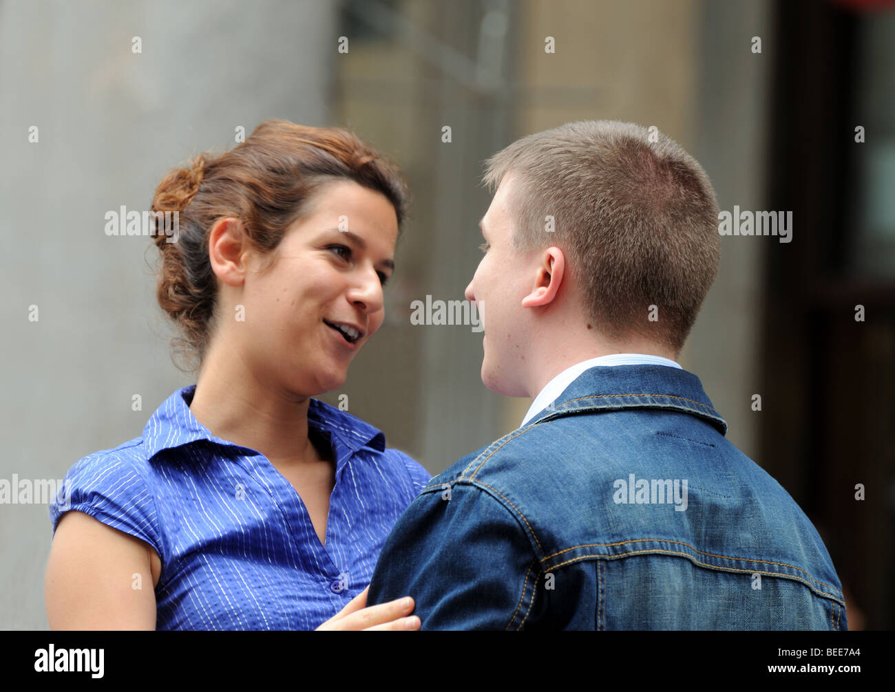 Young couple boy and girl meet and embrace at junction of Piazza del Duomo and Corso Vittorio Emanuele II Milan - Stock Image