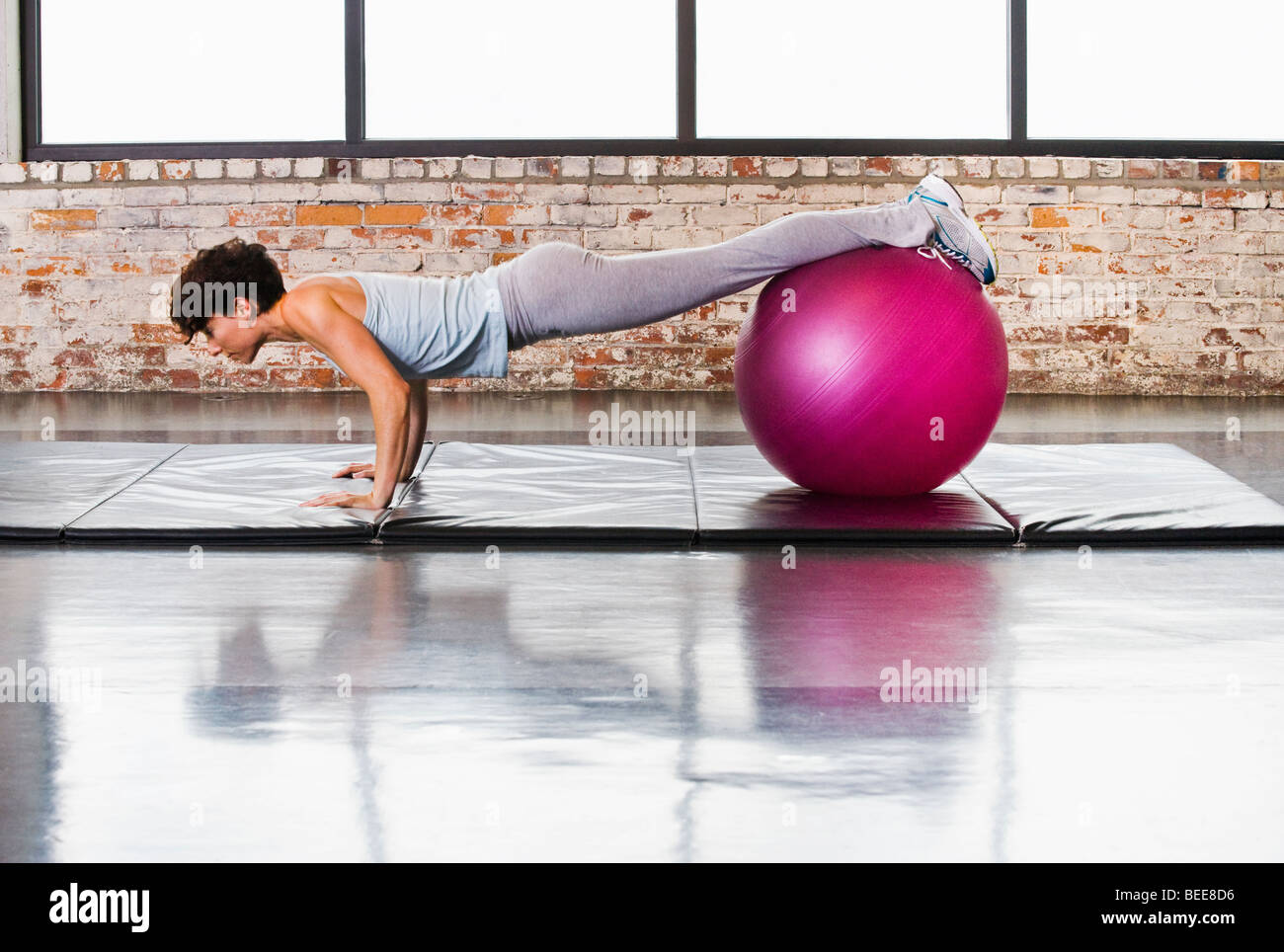 A young woman doing pushups on a mat in a healthclub while balancing her legs / feet on a exercise ball. - Stock Image