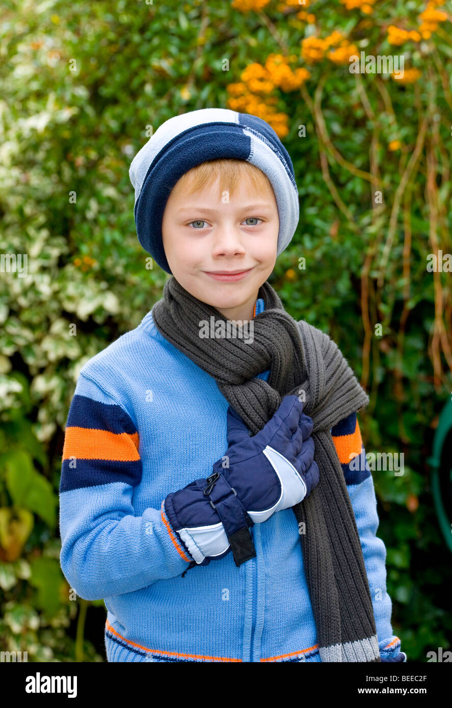 6-year-old boy wearing a hat, scarf and gloves - Stock Image