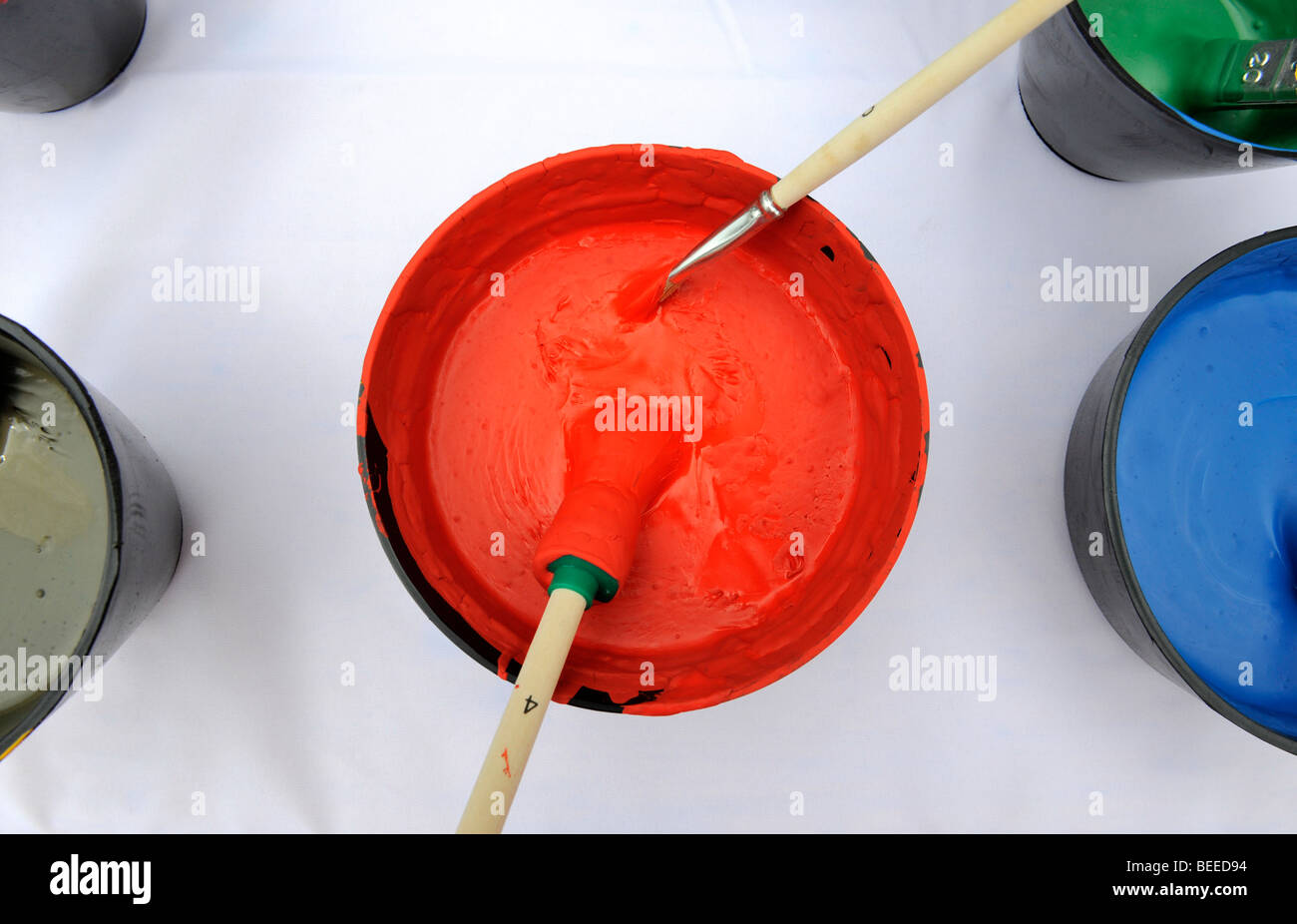 Can of red paint with two brushes - Stock Image