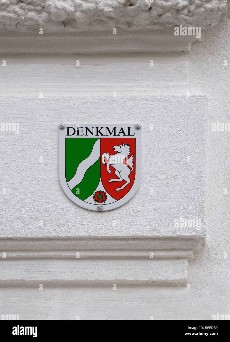 Sign for a protected monument of North Rhine-Westphalia on a white decorated facade - Stock Image