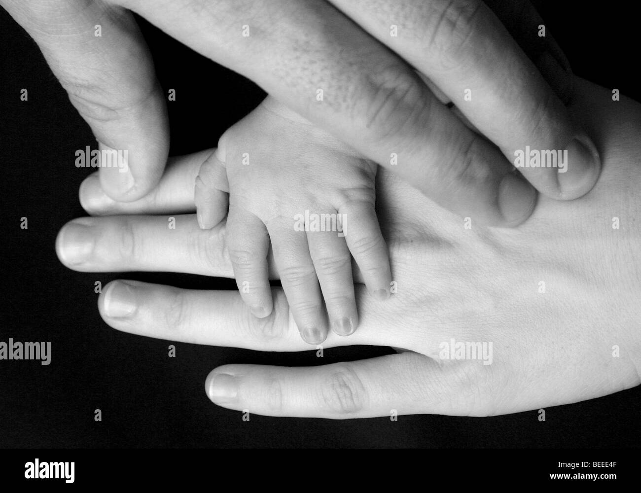 Hands Of A Family Father Mother And Three Week Old Baby Stock